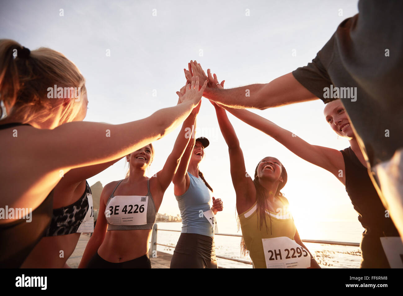 Runners high fiving each other after a good training session. Group of athletes give each other high five after - Stock Image