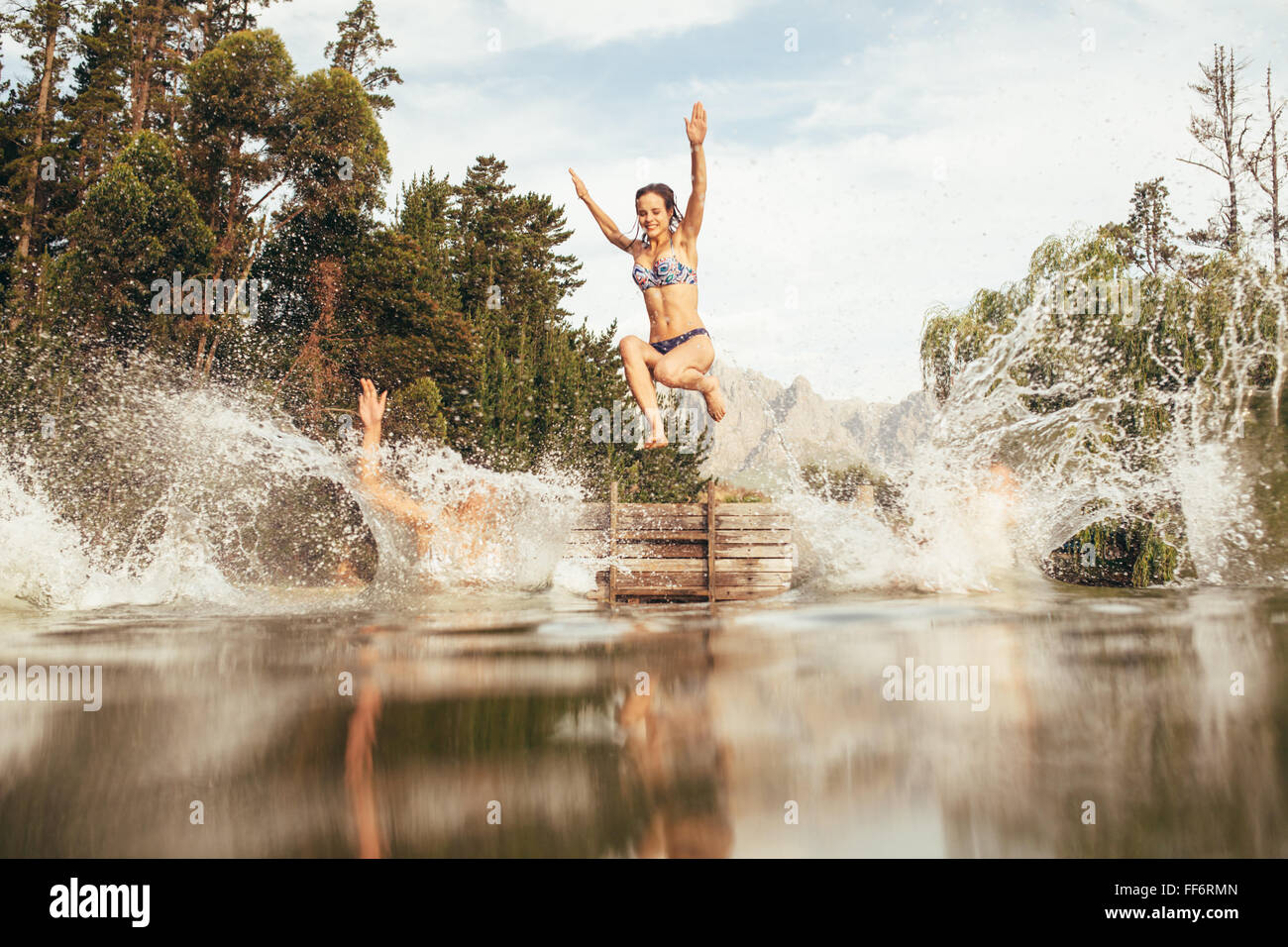 Portrait of young women jumping into a wilderness lake from the jetty. Young girl jumping from a pier at the lake - Stock Image