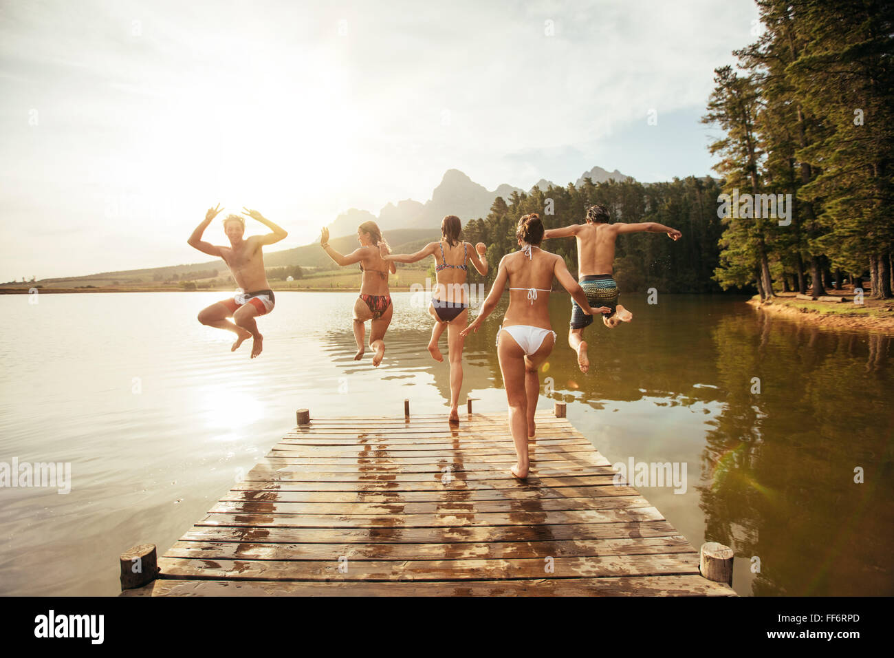 Rear view portrait of young friends jumping into a lake. Young people running and jumping from a jetty in to a lake - Stock Image
