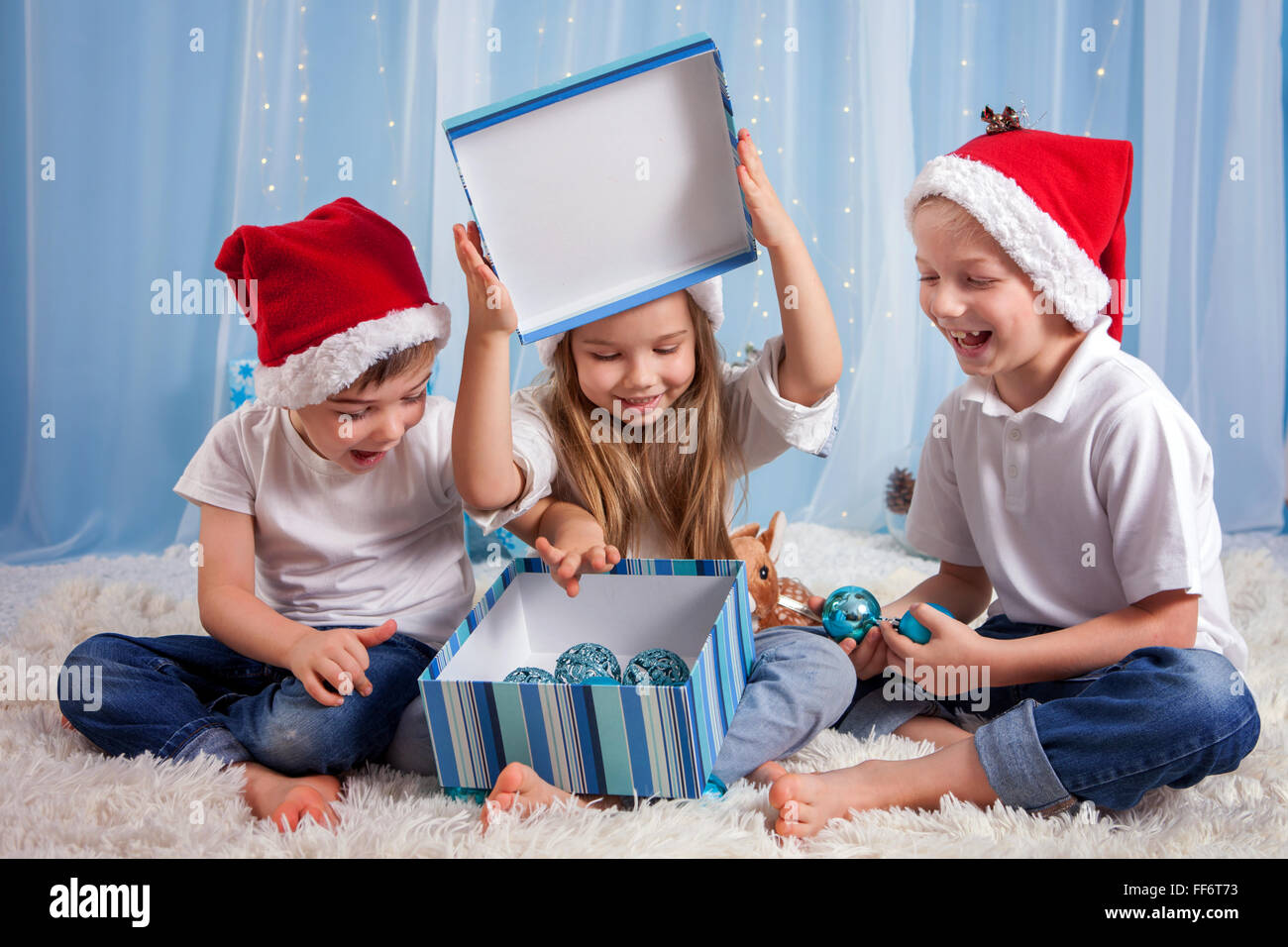Three adorable kids, preschool children, siblings, having fun for Christmas, opening box with decoration, studio - Stock Image