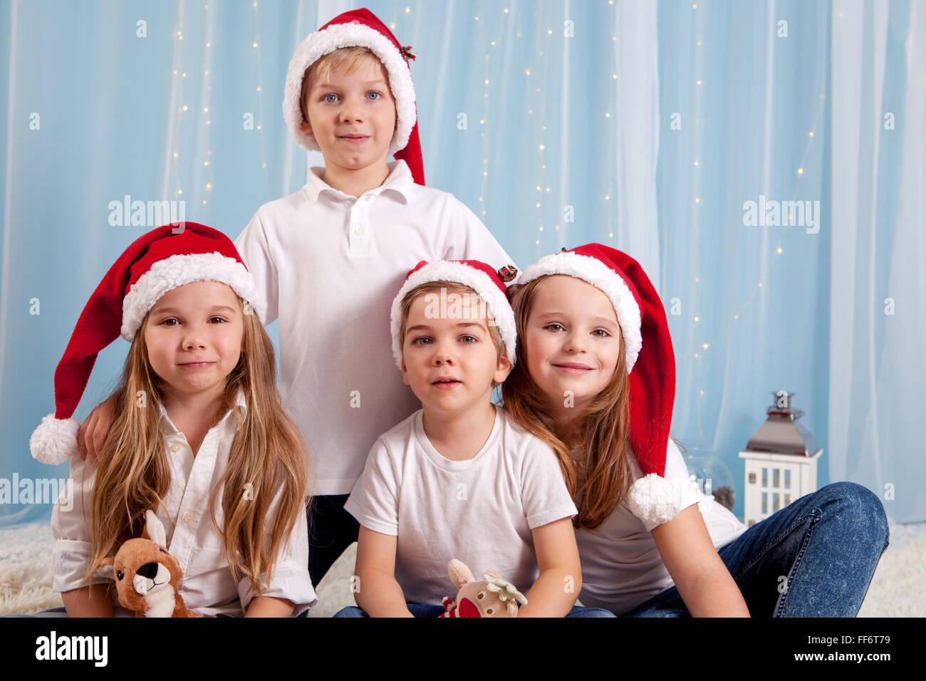 Four adorable kids, preschool children, having fun for christmas, studio shot - Stock Image