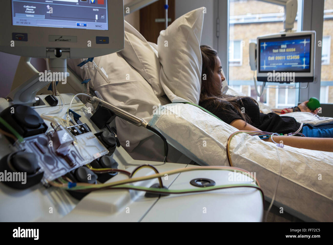 A young female hospital patient lies bed while attached to a medical transfusion device in the London clinic, London, - Stock Image