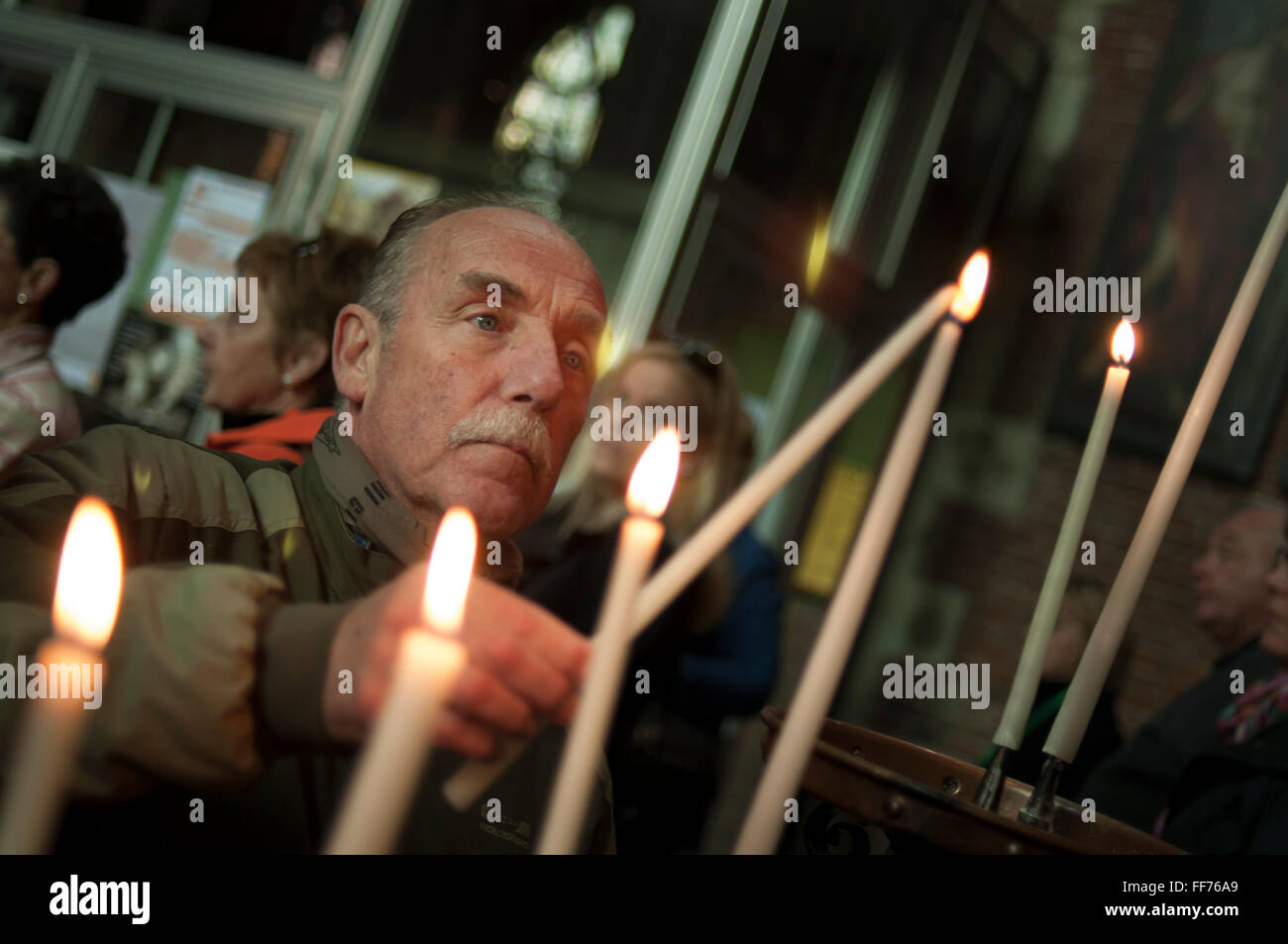 Religious man lighting a candle - Stock Image