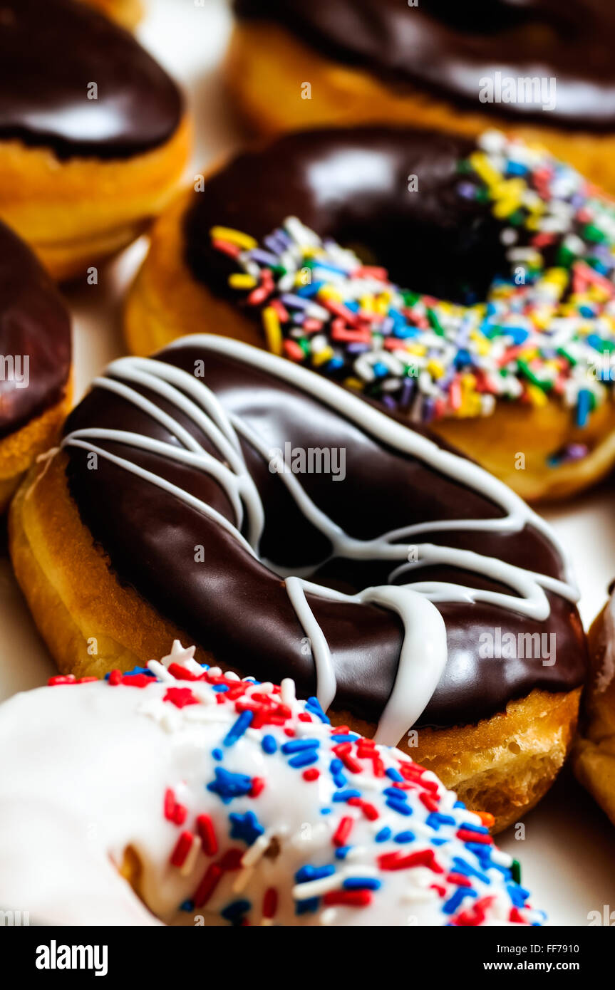 Assorted doughnuts in a vertical row close up Stock Photo