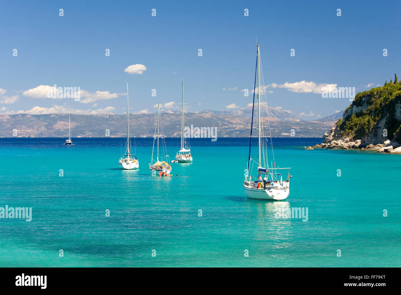 Lakka, Paxos, Ionian Islands, Greece. View across the clear turquoise waters of Lakka Bay, yachts anchored offshore. - Stock Image