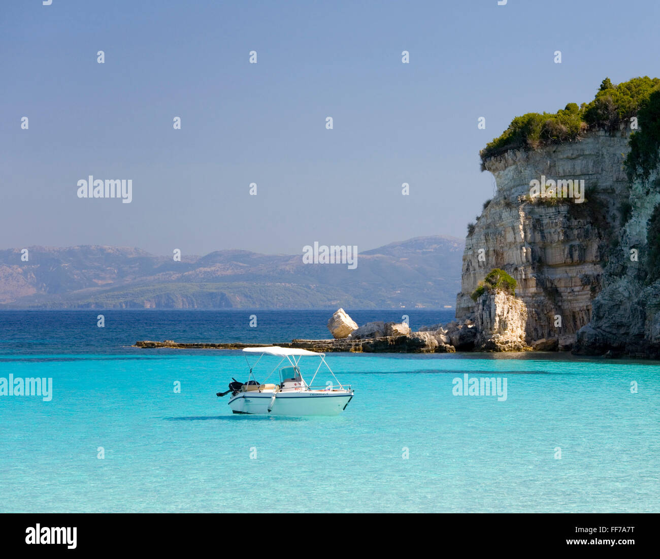 Antipaxos, Ionian Islands, Greece. View across secluded Voutoumi Bay, solitary boat at anchor. - Stock Image