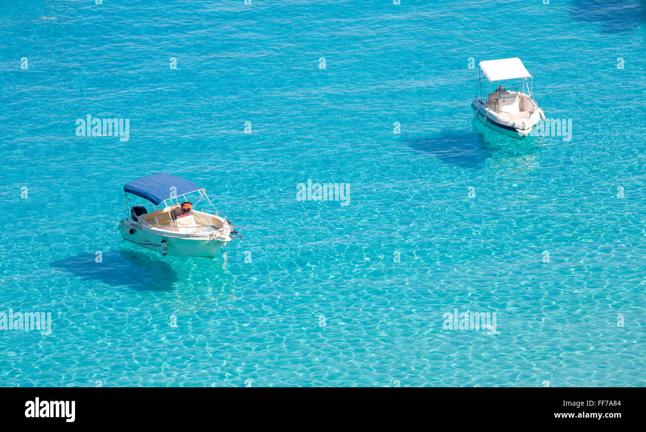 Antipaxos, Ionian Islands, Greece. Two small boats anchored in the clear turquoise waters of Voutoumi Bay. - Stock Image