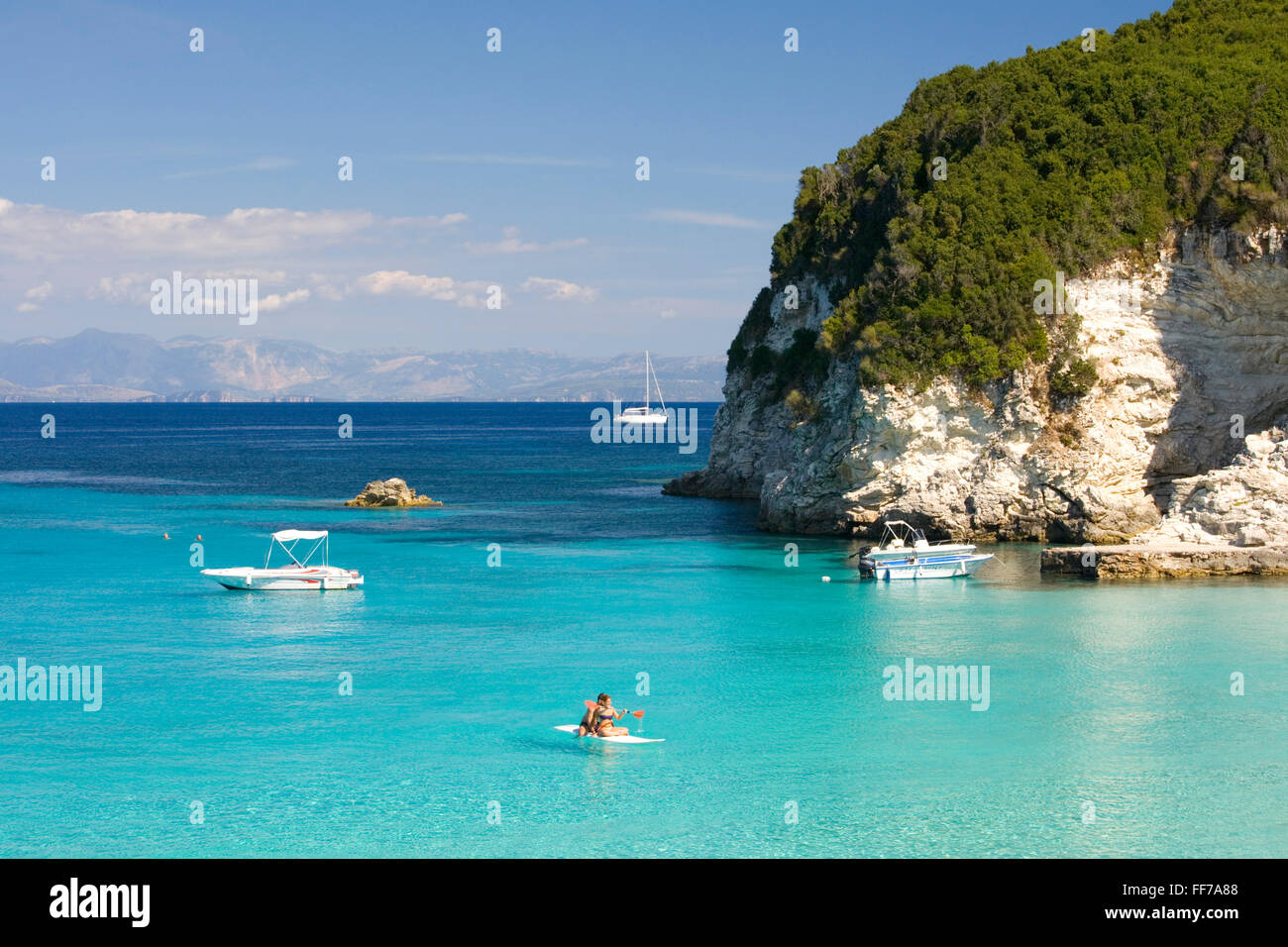 Antipaxos, Ionian Islands, Greece. Couple on paddleboard crossing the clear turquoise waters of Vrika Bay. - Stock Image