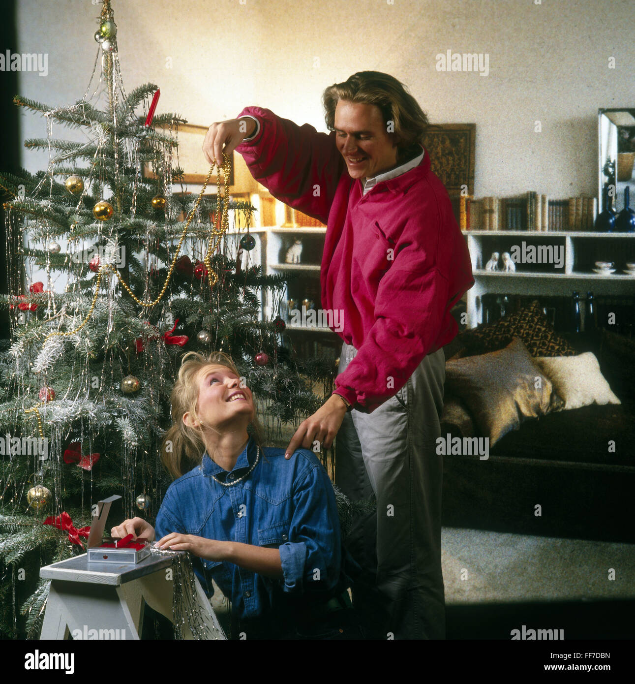 christmas christmas tree christmas tree decorations young couple decorating christmas tree 1980s - 1980s Christmas Decorations