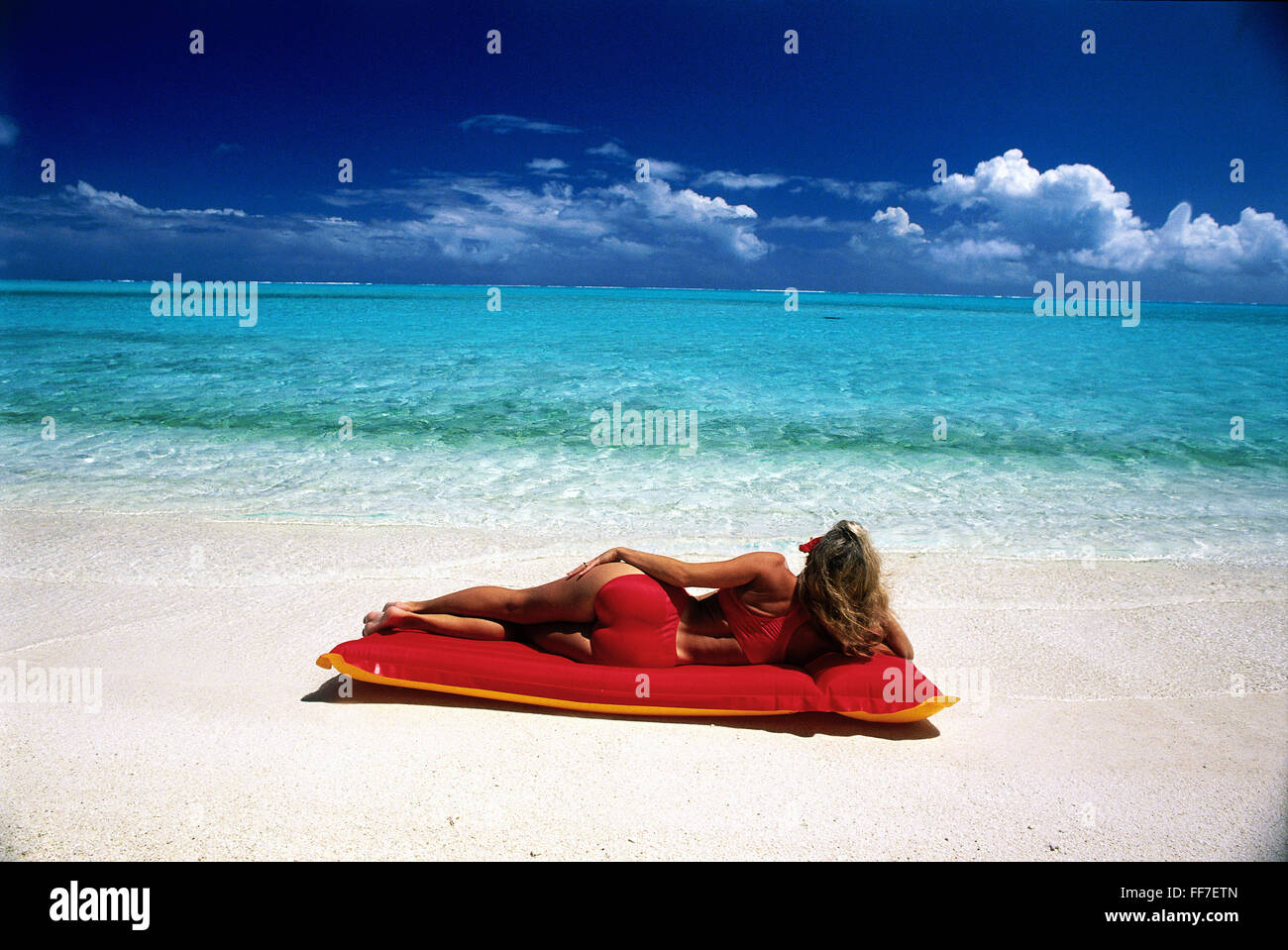leisure time, bathing, woman lying on red air mattress on the beach, circa 1988, Additional-Rights-Clearences-NA - Stock Image