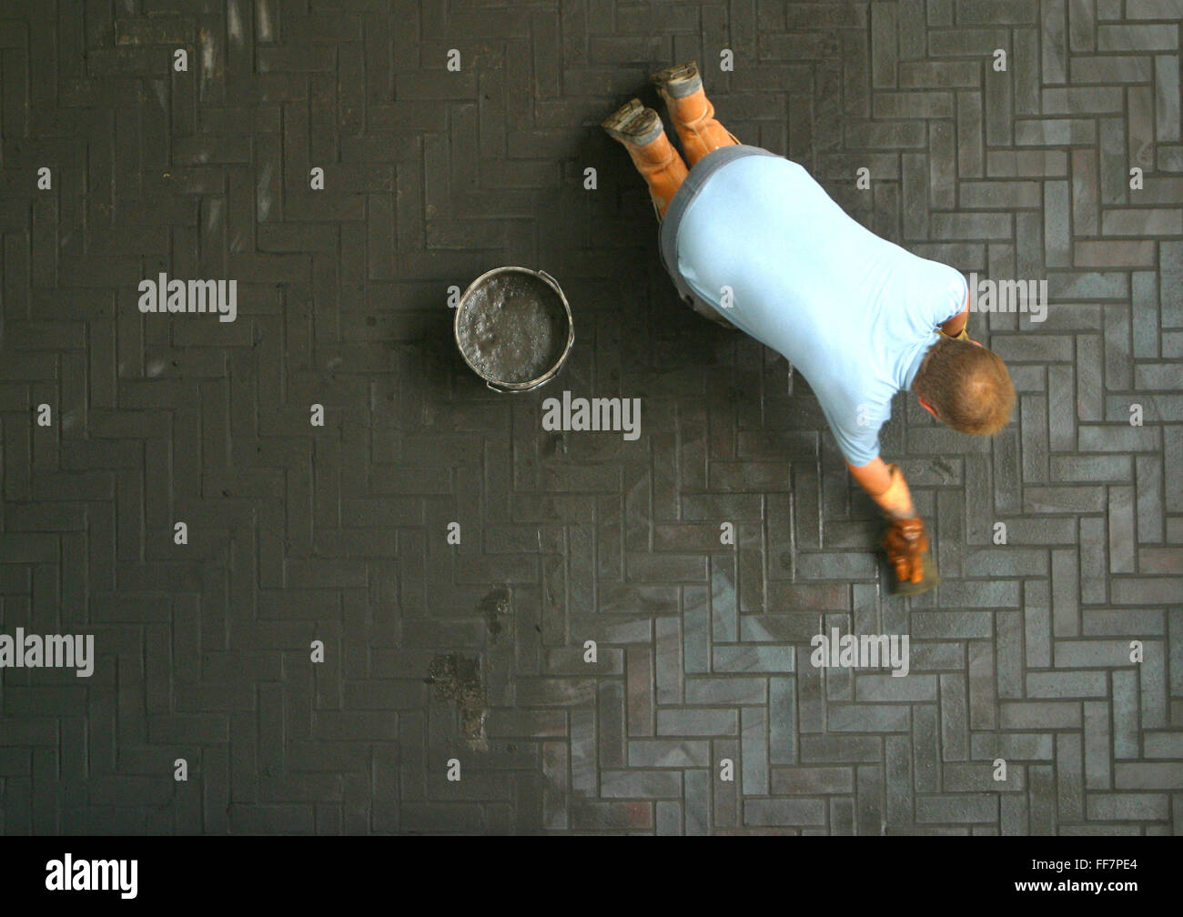 A workman grouts floor tiles during the construction of the East London Childcare Institute, Stratford, London. - Stock Image