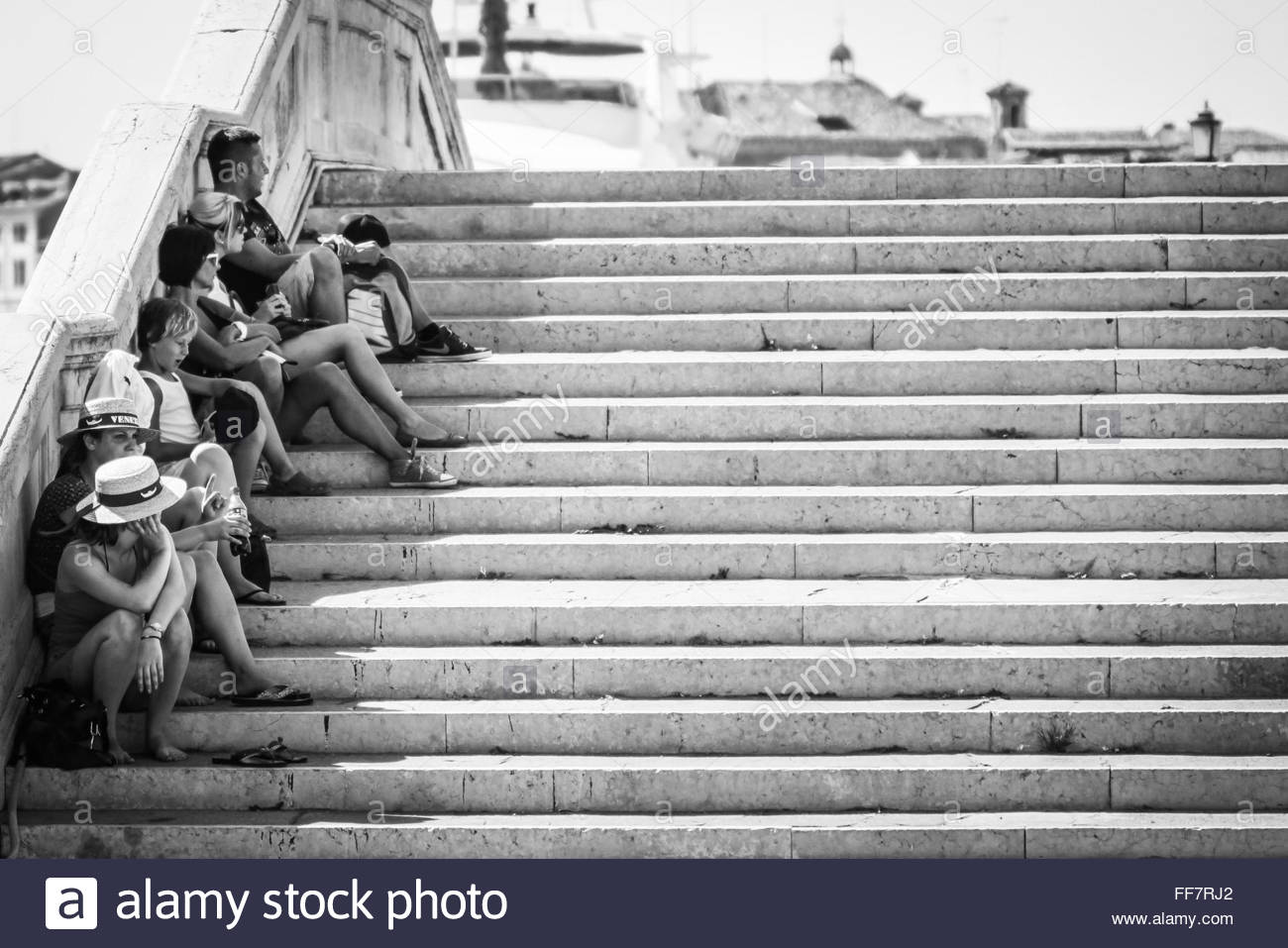 VENICE, ITALY -  2 AUGUST 2012:  Monochrome image of tourists sitting in the shade of a bridge on a hot summer's - Stock Image