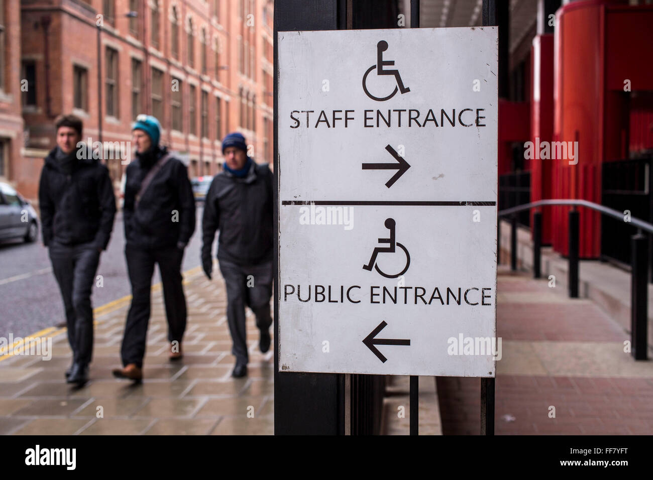 Two disability access signs outside the British Library, London, United Kingdom.  One guides the way to the accessible - Stock Image