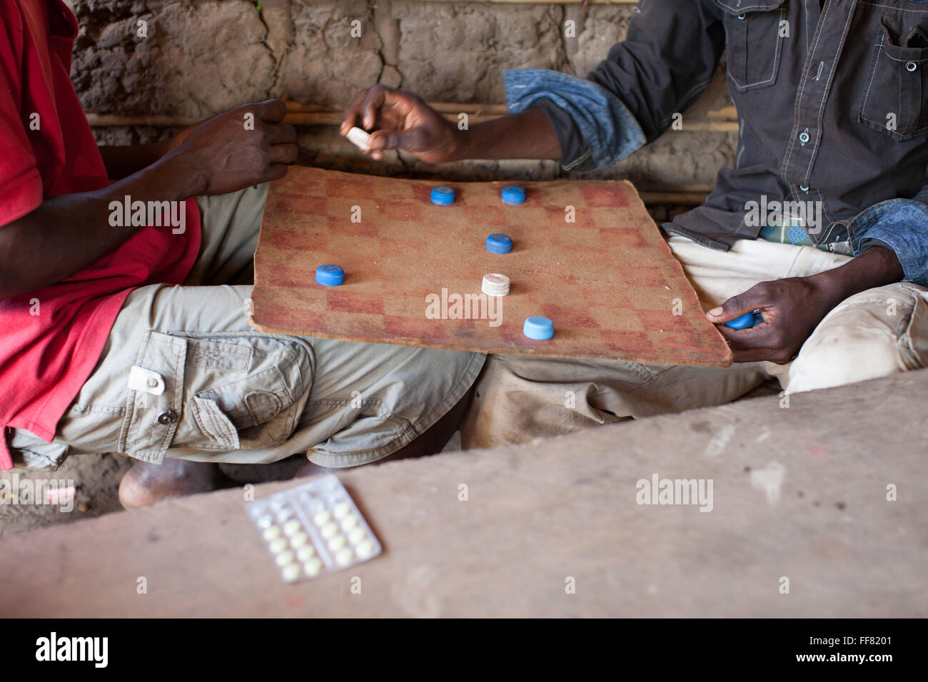 A packet of antimalarial drugs next to two men playing a game of draughts with bottle tops. - Stock Image