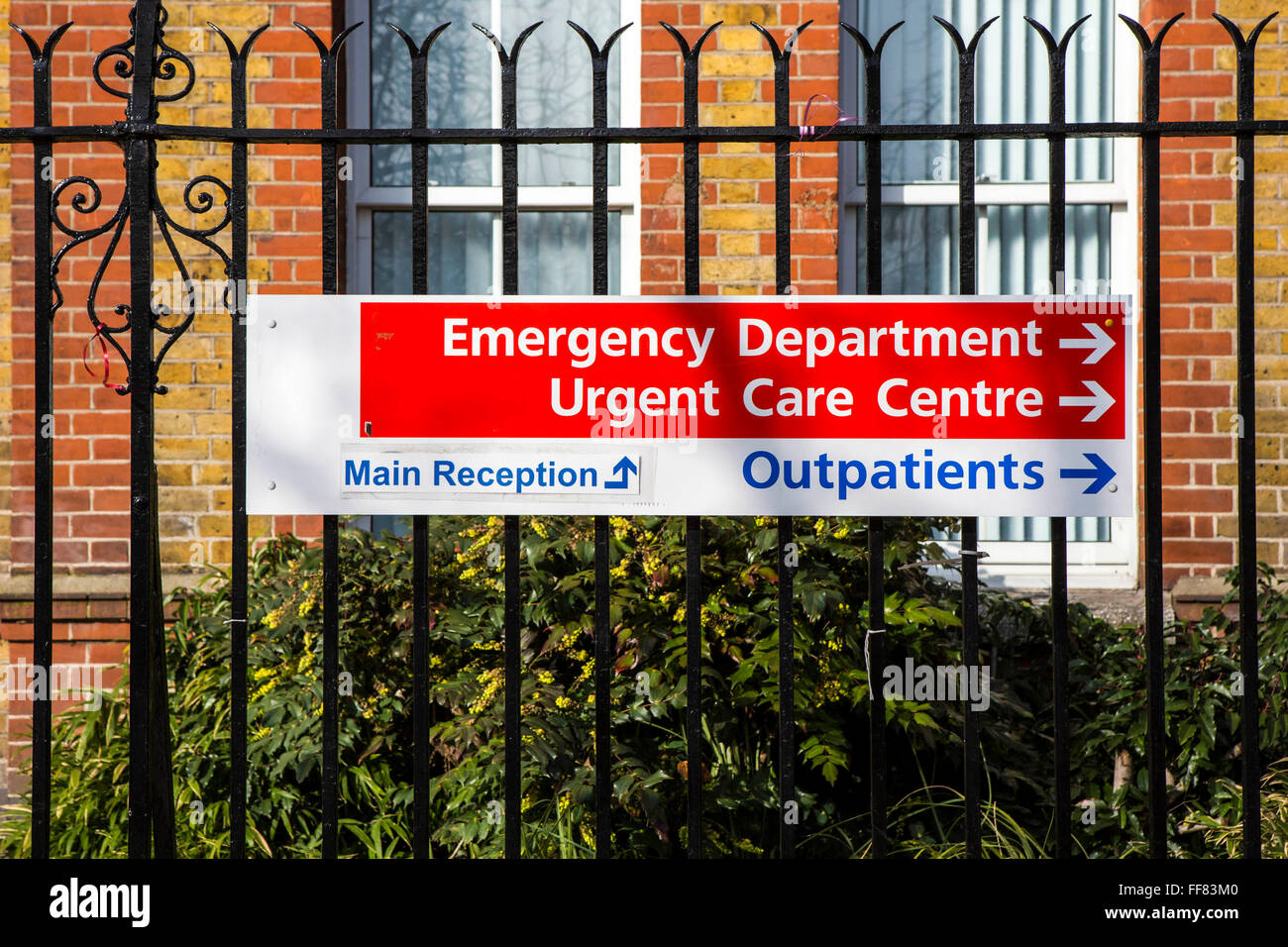 Public sign on metal fence directing people to the Emergency Department, Urgent Care Centre, Outpatients and Main - Stock Image