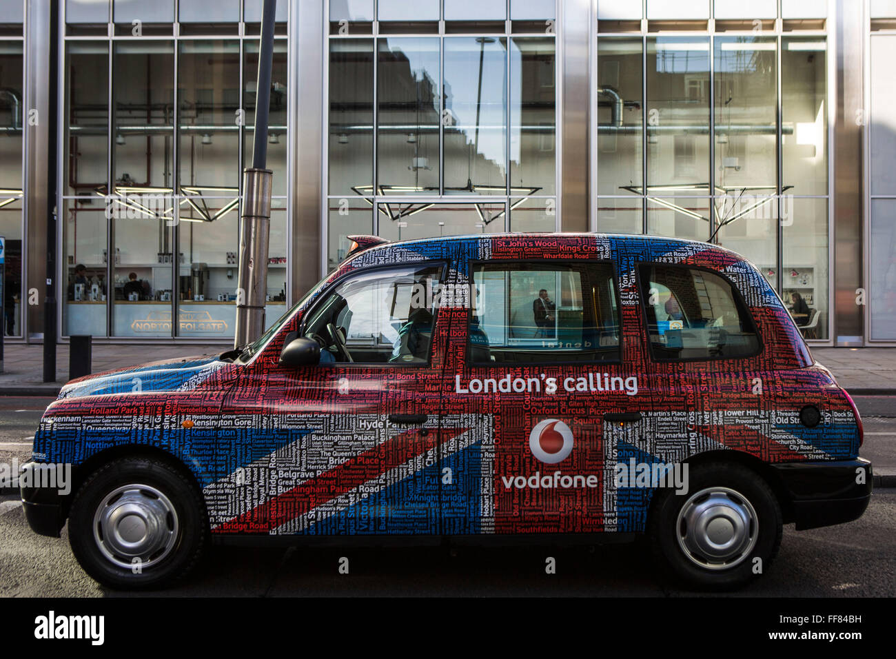 A traditional London Hackney carriage taxi cab advertising Vodafone, a multi-national mobile communication business. - Stock Image