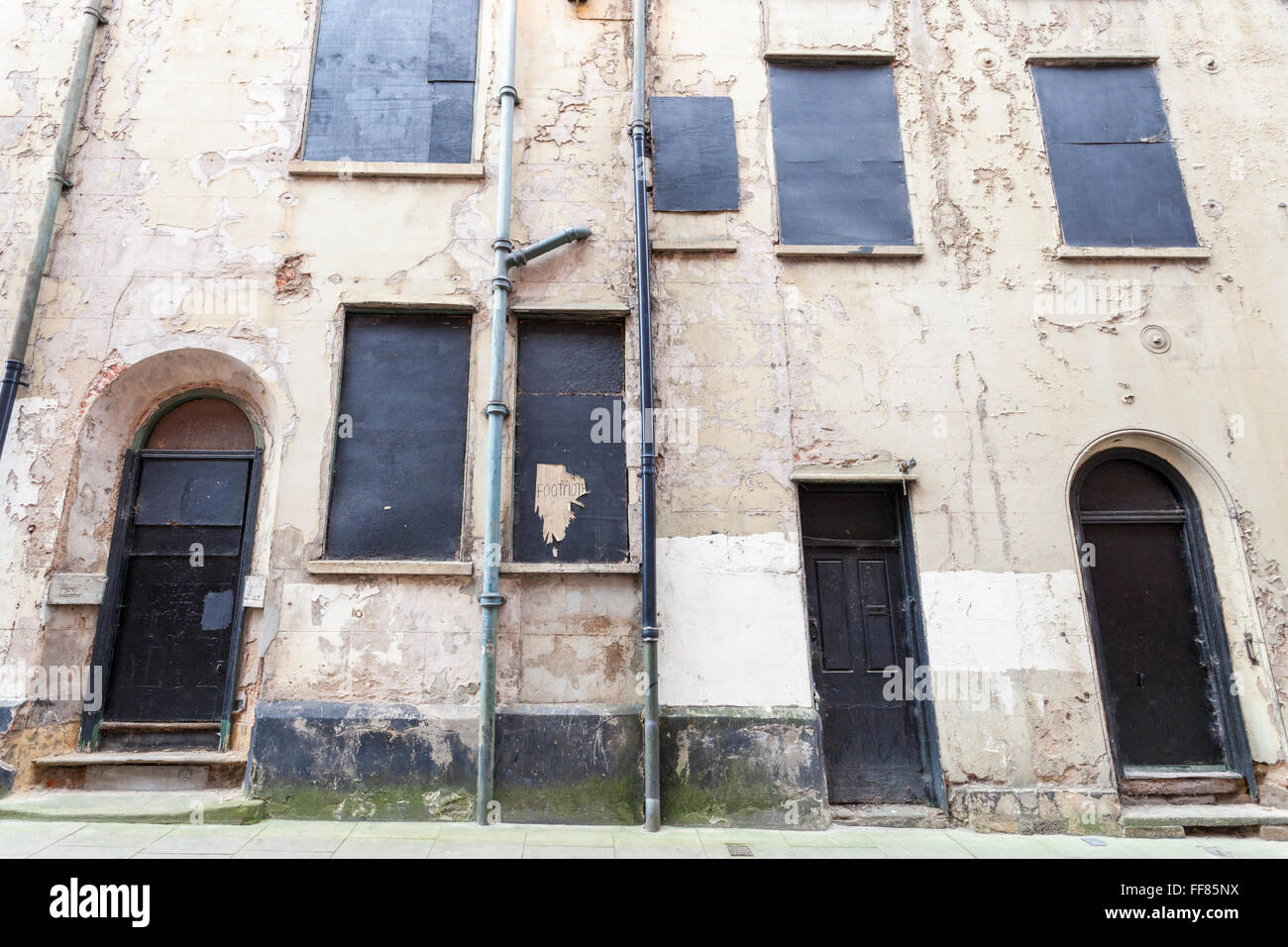 Wall and boarded up windows and doors on a 17th century town house that has fallen into disrepair, Nottingham, England, - Stock Image