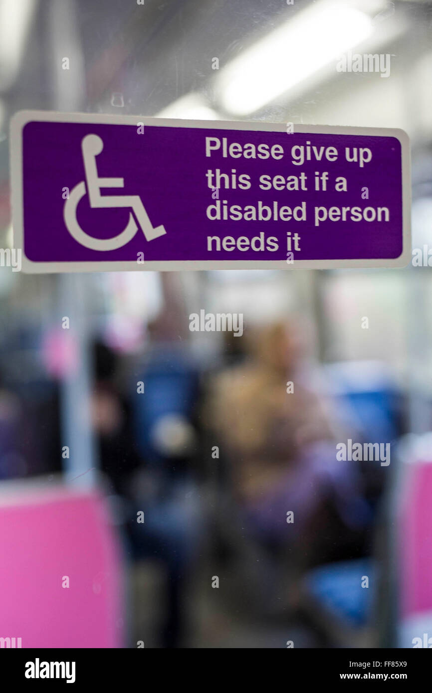 A disability sign on a Greater Anglia train requesting customers give up a seat for disabled person. UK. - Stock Image
