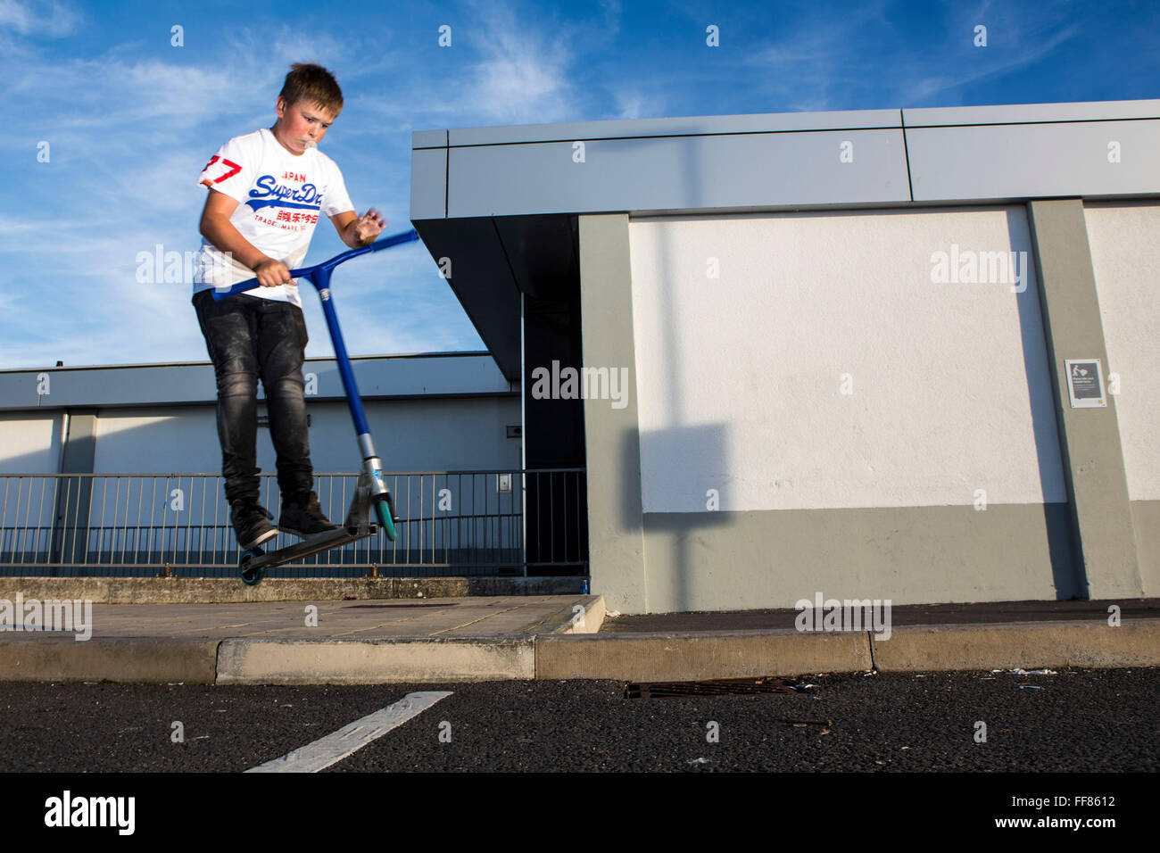 A Wadebridge youngster scootering in Lidl car park. WREN community energy has given funding received from the Feed - Stock Image
