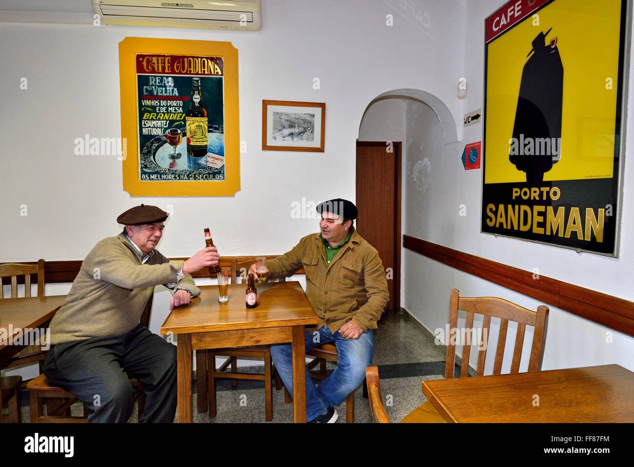 Portugal, Alentejo: Two native men having a beer and a chat in the traditional Café Guadiana in Mértola - Stock Image
