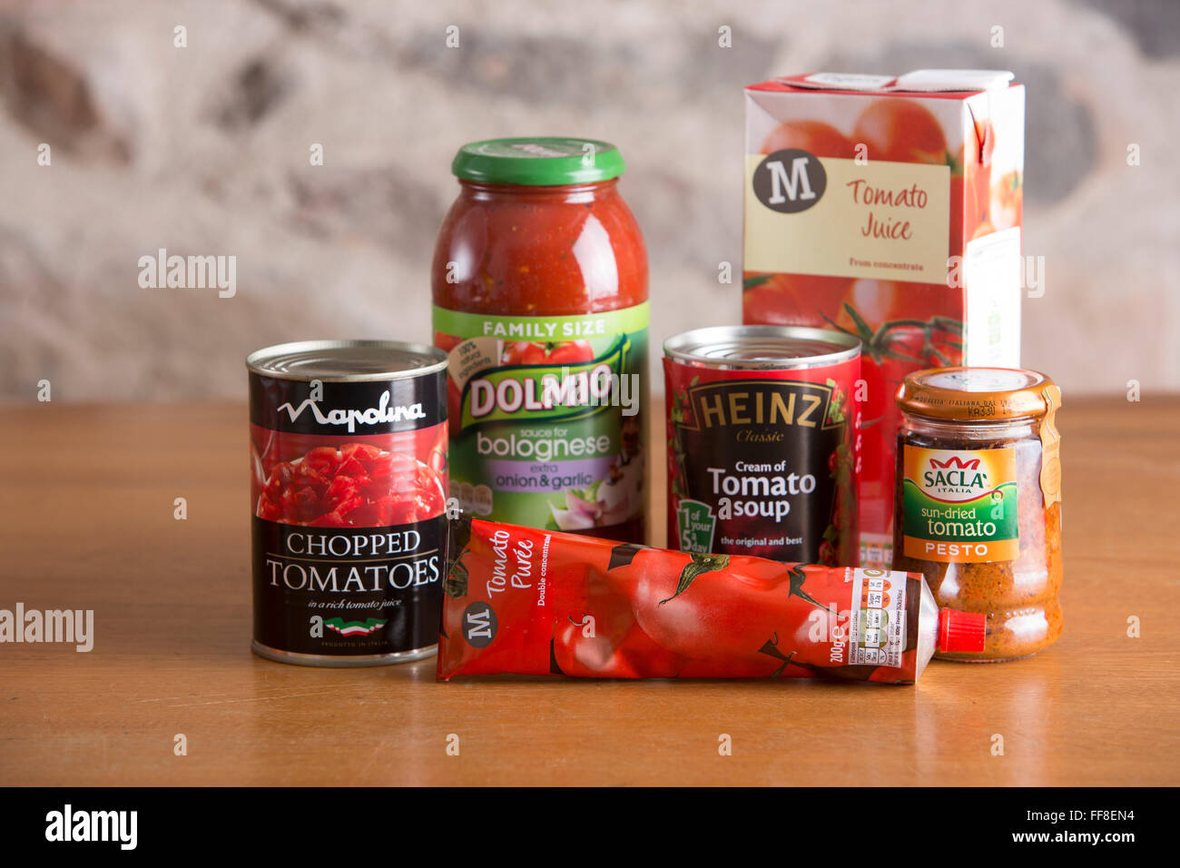 Selection of preserved tomato products including soup, juice, sauce, puree and canned all sitting on a country kitchen - Stock Image