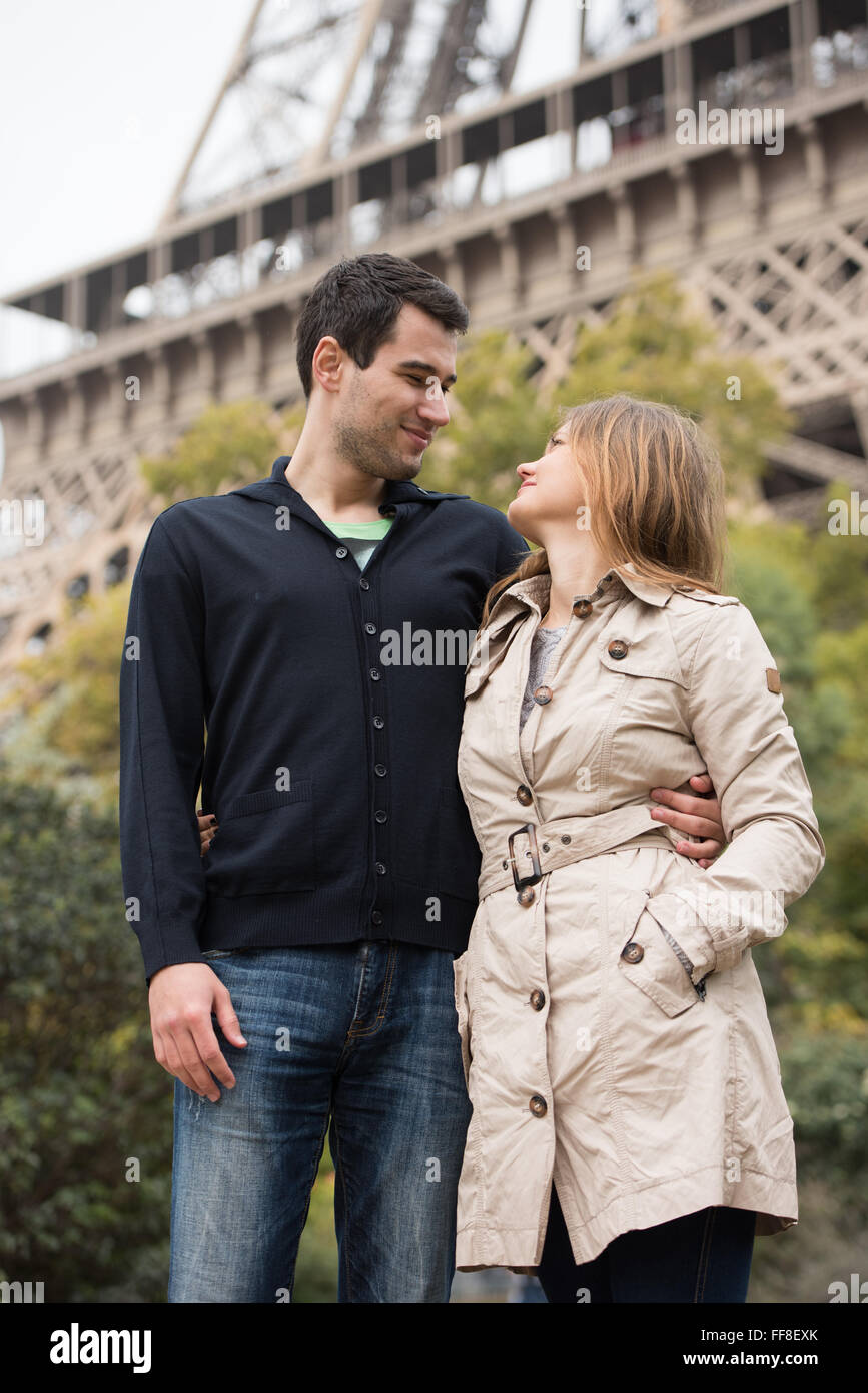 young couple, man and woman standing in front of Eifel tower, Paris, France, looking in each others eyes - Stock Image