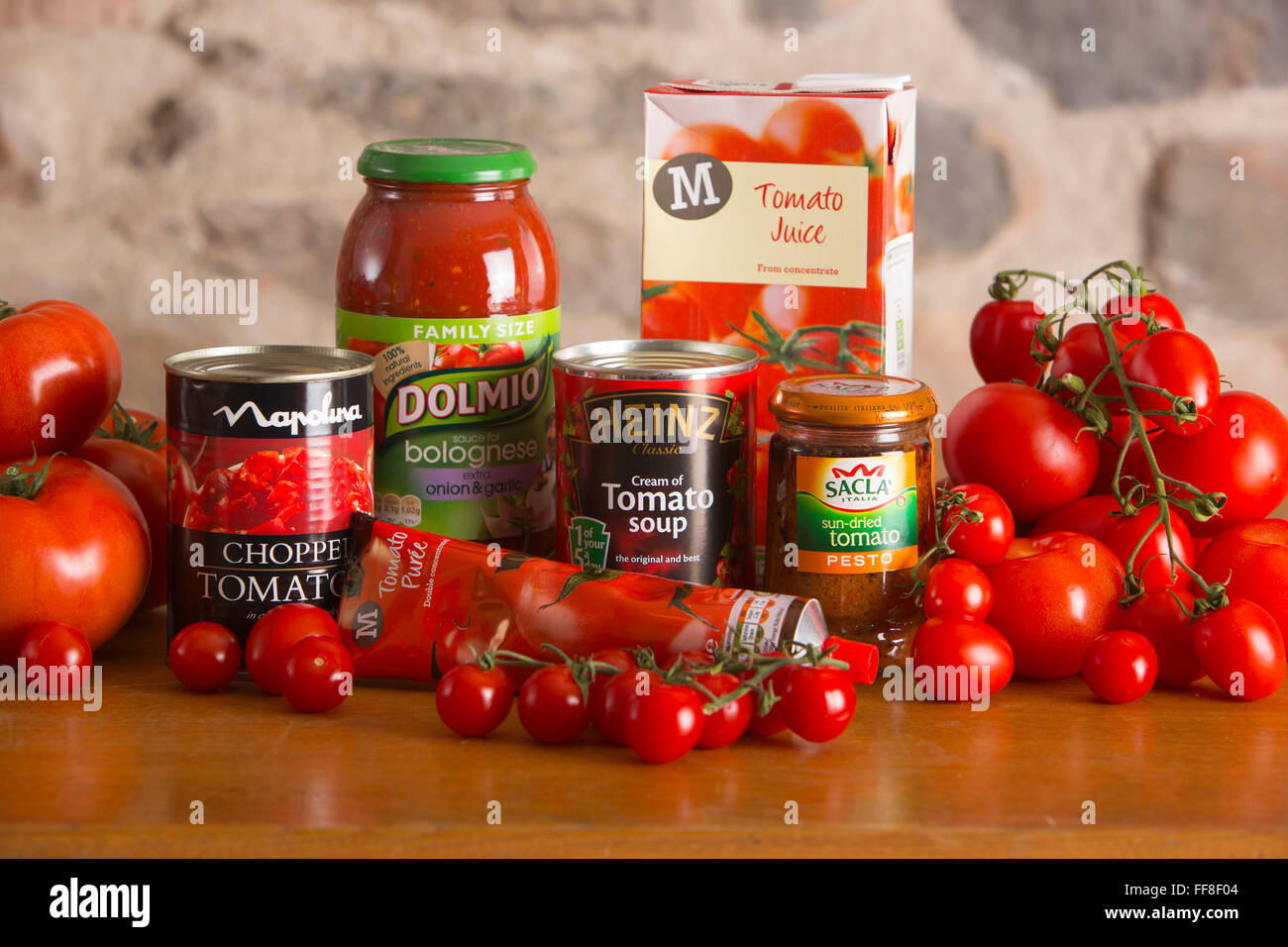 tomatoes and tomato products on a country kitchen table including soup, sauce, juice, puree and pesto - Stock Image