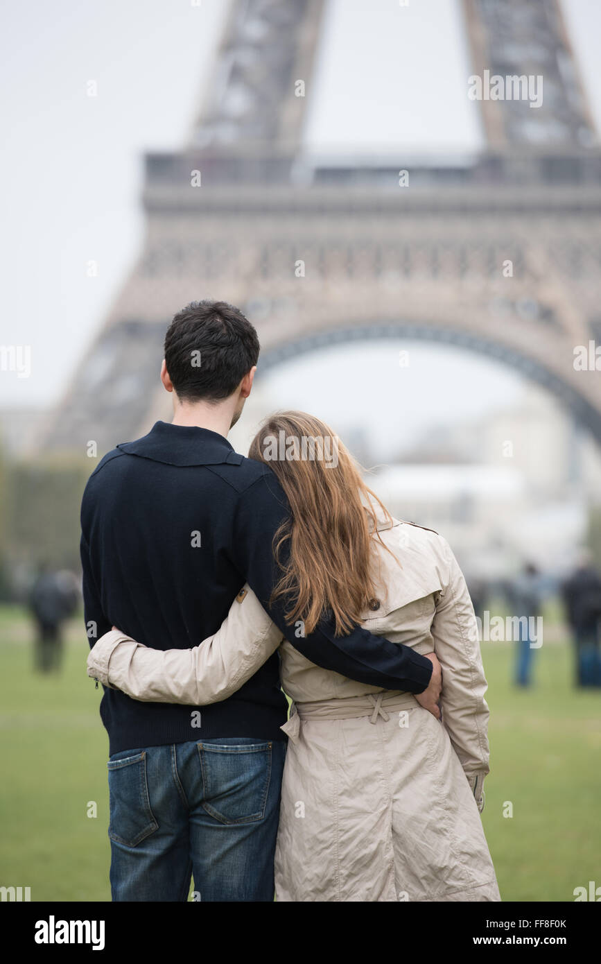 young couple, man and woman standing in front of Eifel tower, Paris, France, hugging - Stock Image