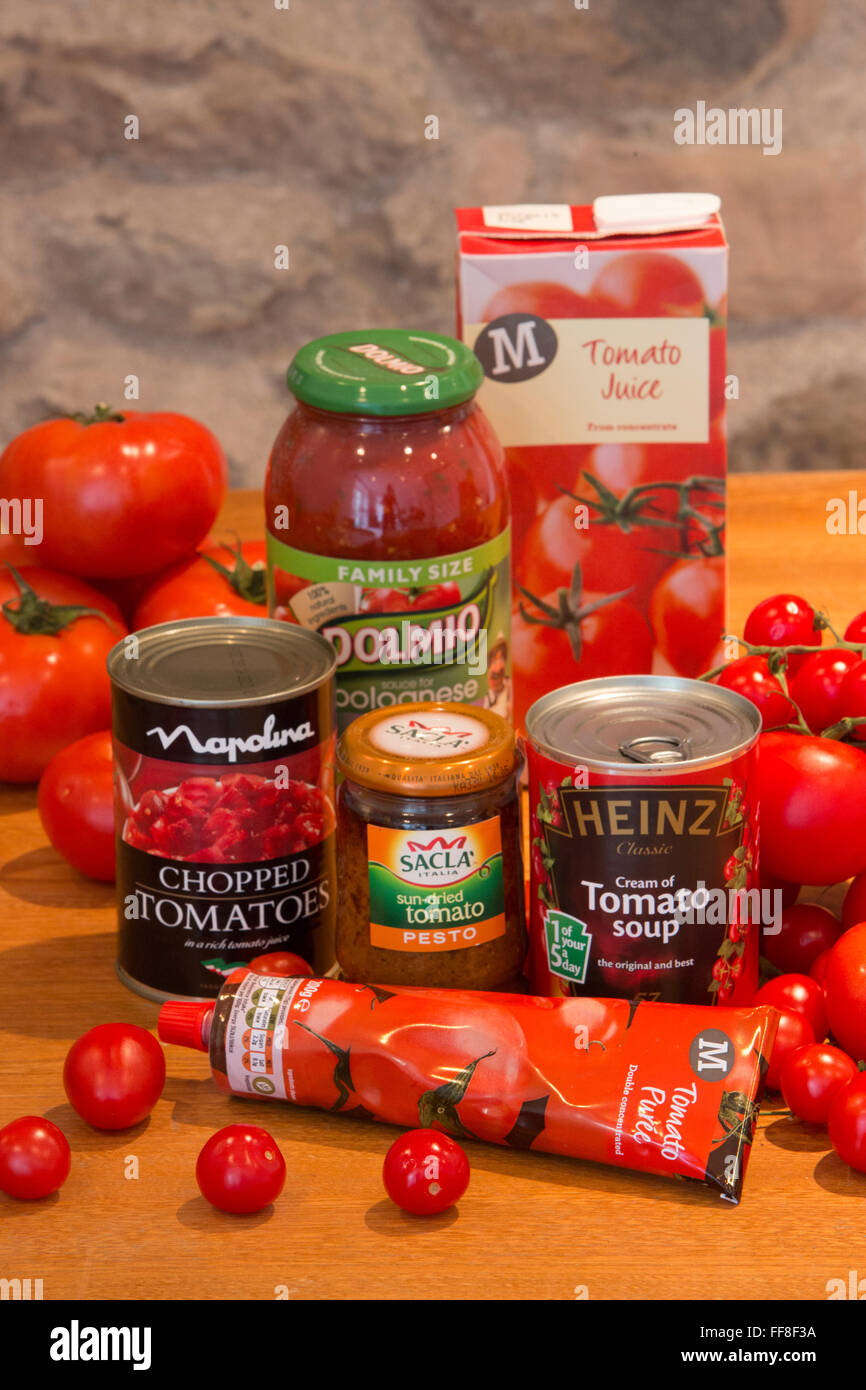 Collection of tomato products including soup, sauce, juice and puree on a country kitchen table - Stock Image
