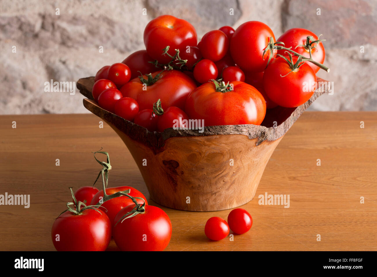 Big bowl of tomatoes sitting on a country kitchen table - Stock Image