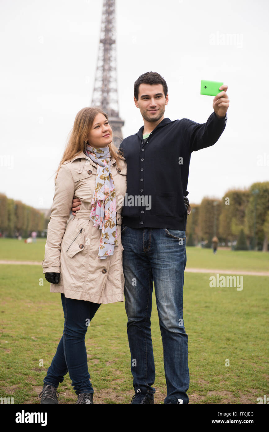 young couple, man and woman making selfie in front of Eifel tower, Paris, France - Stock Image