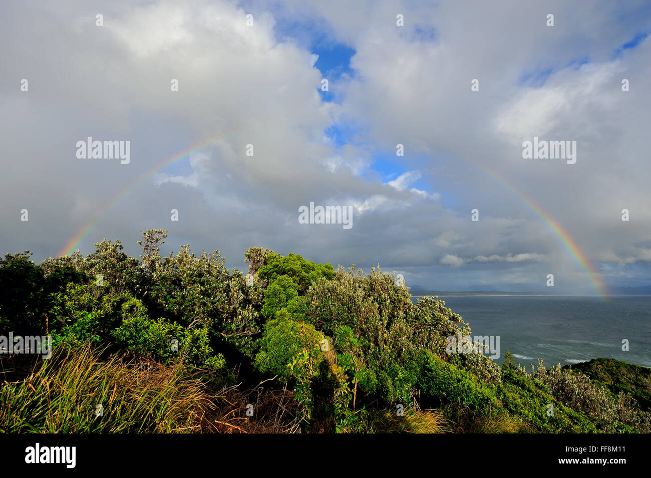 Perfect rainbow over the ocean at Cape Byron - Stock Image
