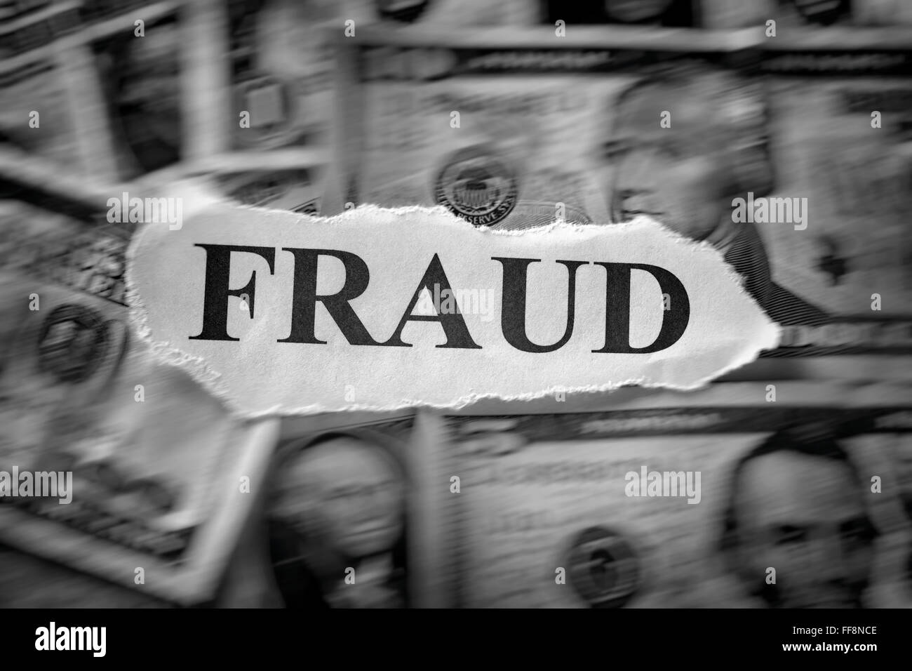 Fraud concept. Torn piece of paper with the word 'Fraud' on dollar bills. Motion blur. Black and White. - Stock Image