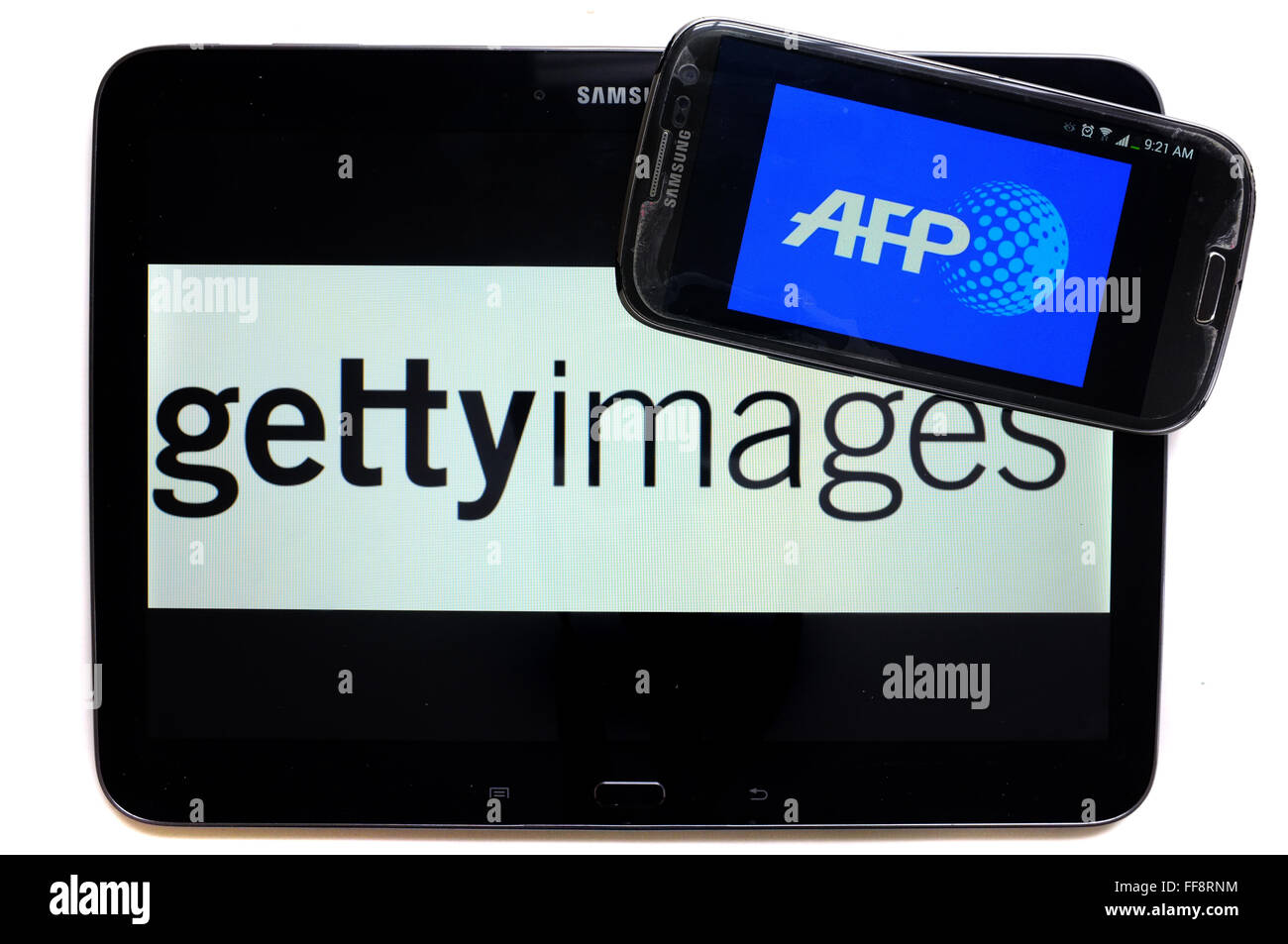 The news agencies AFP and getty images on the screens of a tablet and a smartphone photographed against a white - Stock Image