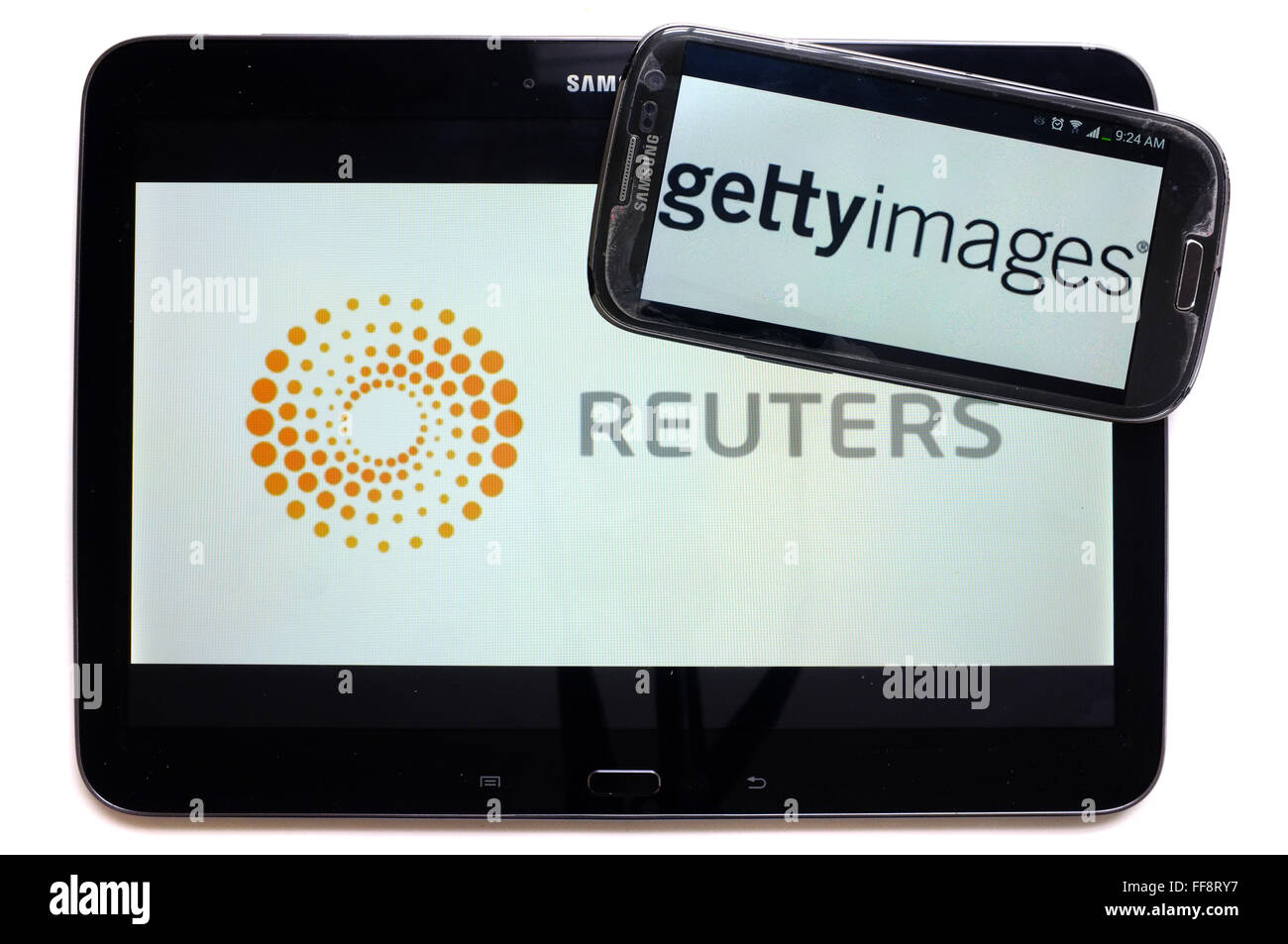 The news agencies getty images and Reuters on the screens of a tablet and a smartphone photographed against a white Stock Photo