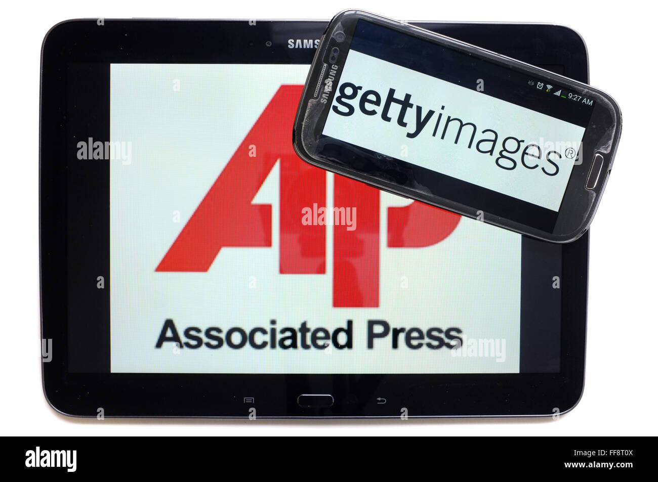 The news agencies AP and getty images on the screens of a tablet and a smartphone photographed against a white background. - Stock Image