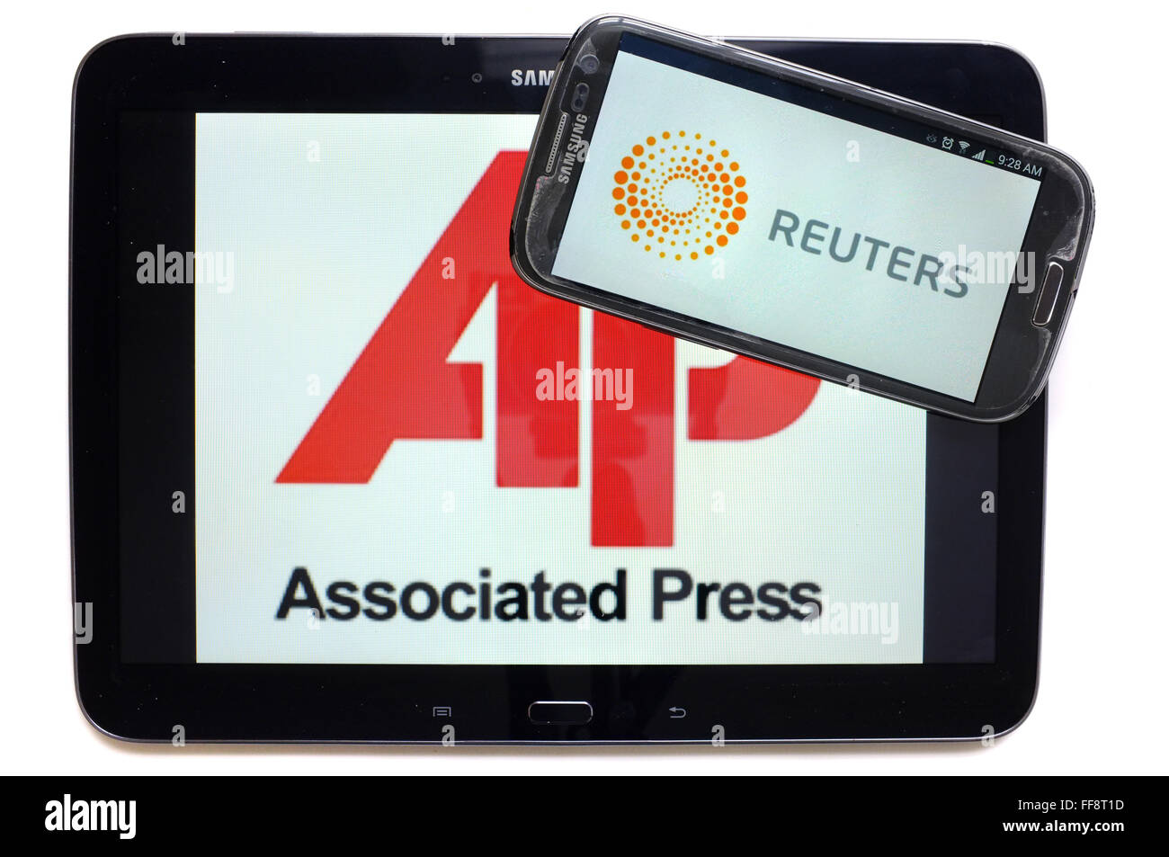 The news agencies AP and Reuters on the screens of a tablet and a smartphone photographed against a white background. - Stock Image