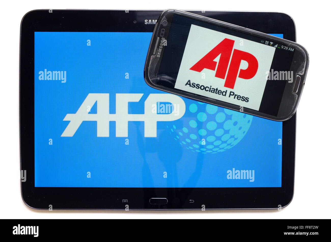The news agencies AFP and AP on the screens of a tablet and a smartphone photographed against a white background. - Stock Image