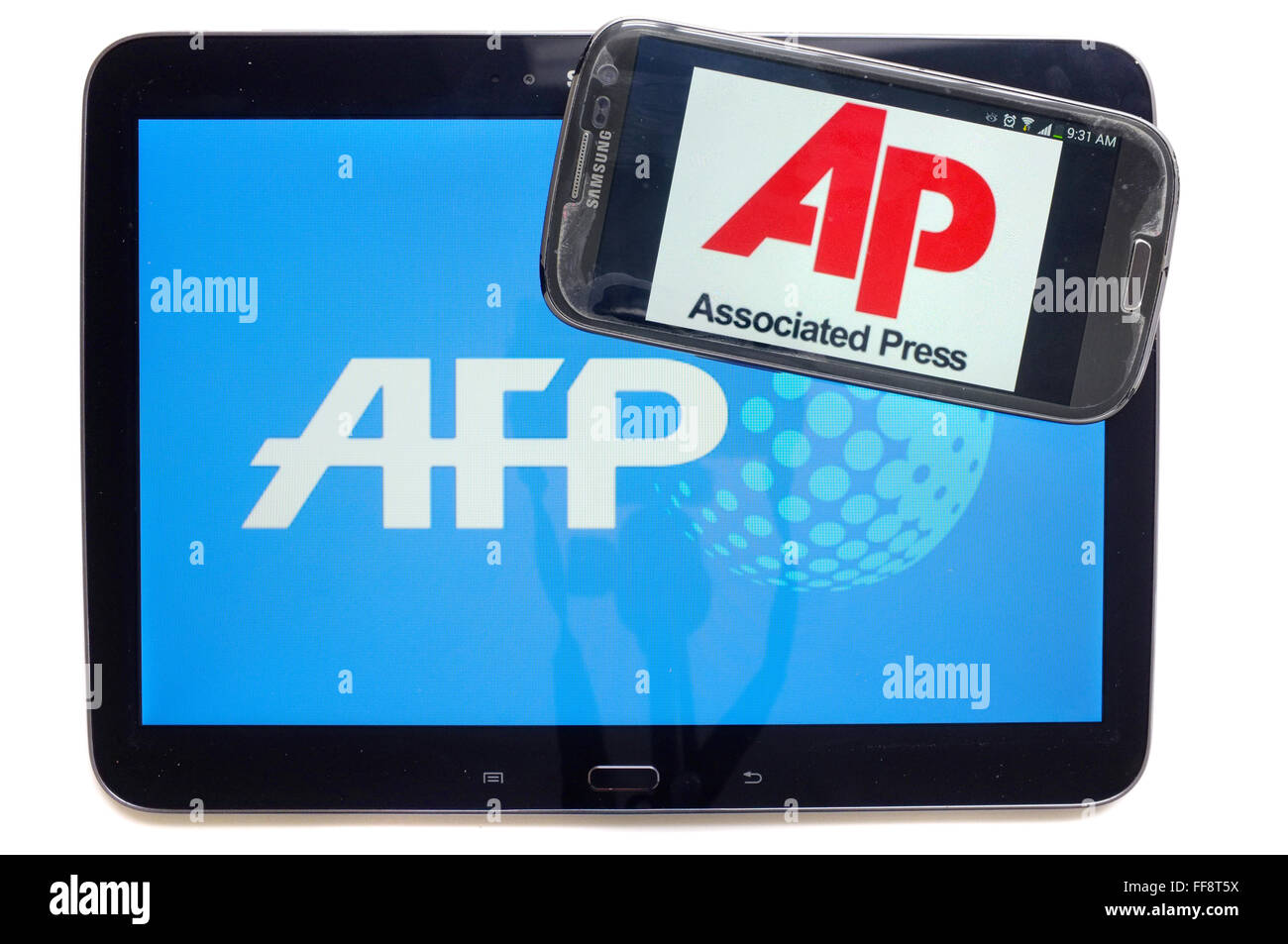 The AP logo on a smartphone screen on top of a tablet displaying the AFP logo photographed against a white background. - Stock Image