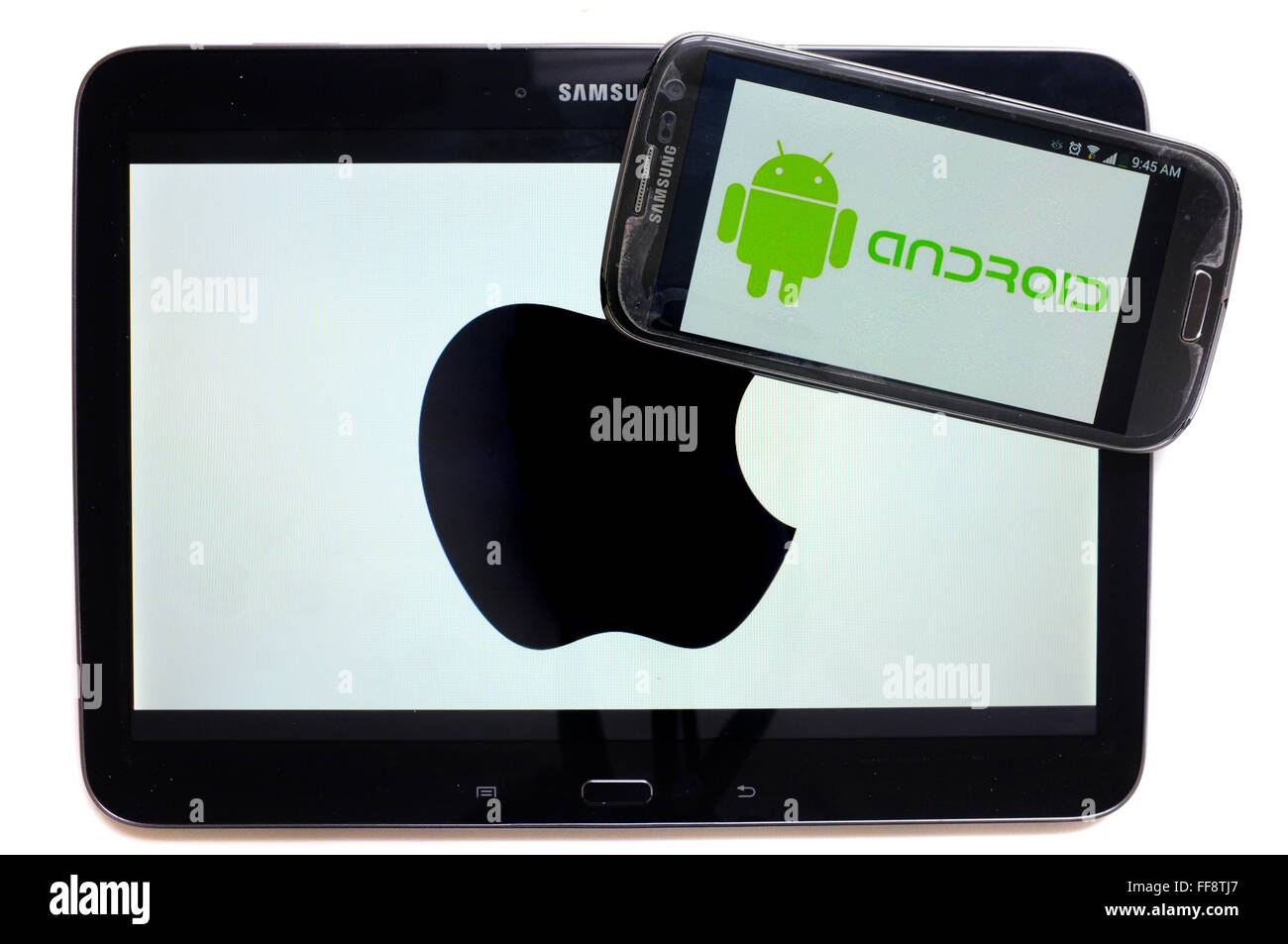 The Android logo on a smartphone screen on top of a tablet displaying the Apple logo photographed against a white - Stock Image