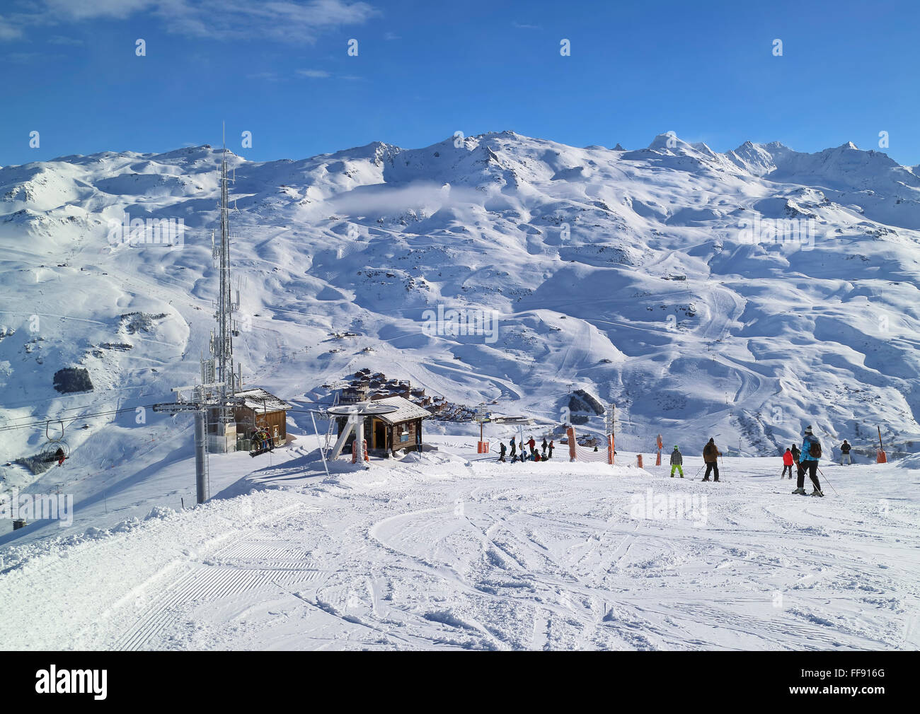 Les Menuires, Alps, France - February 04 2016: People skiing and snowboarding downhill on Masse piste above Les - Stock Image