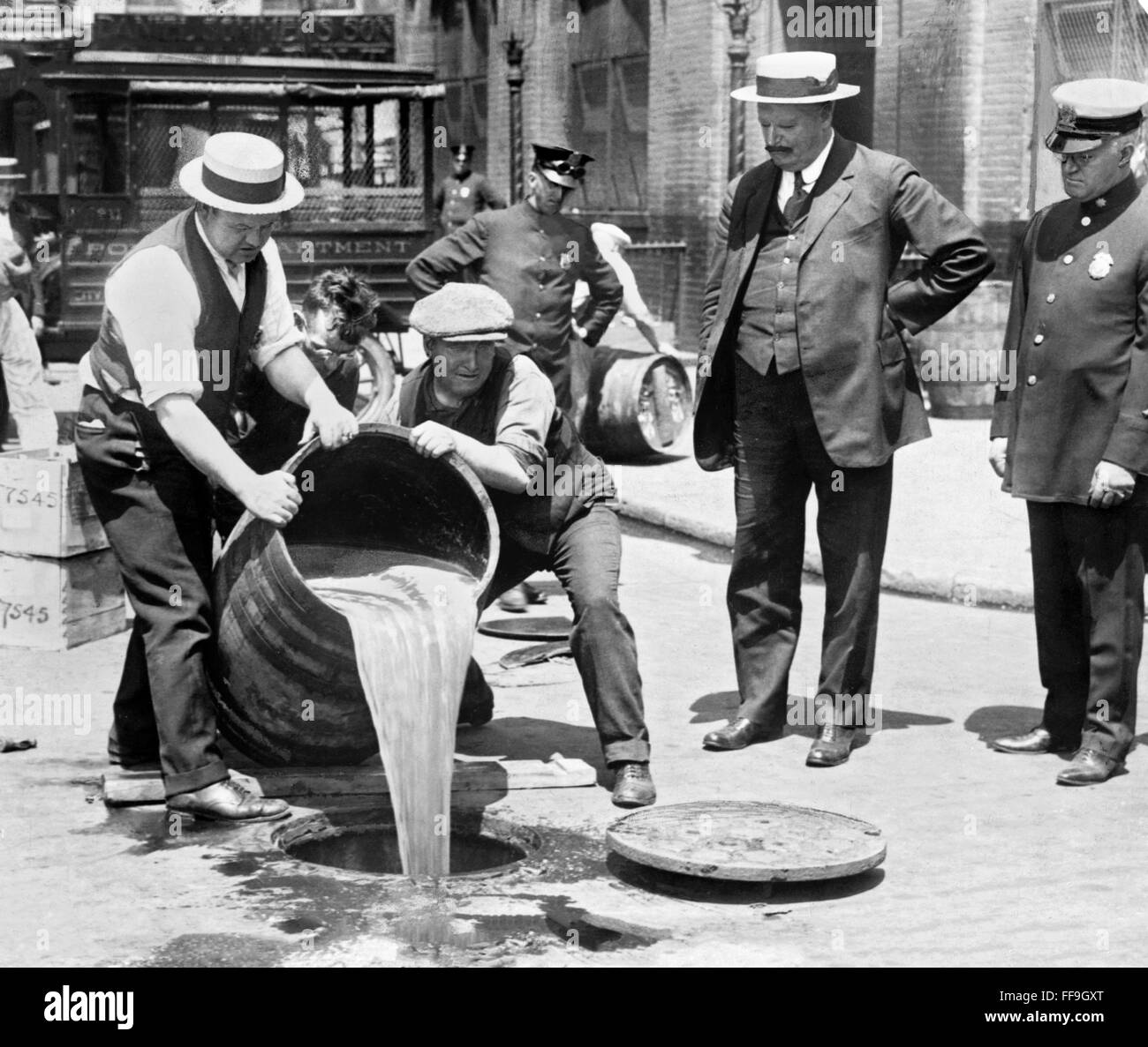 Prohibition 1920s. Agents pouring liquor into sewer following a raid during probibition, New York City, NY, USA. - Stock Image