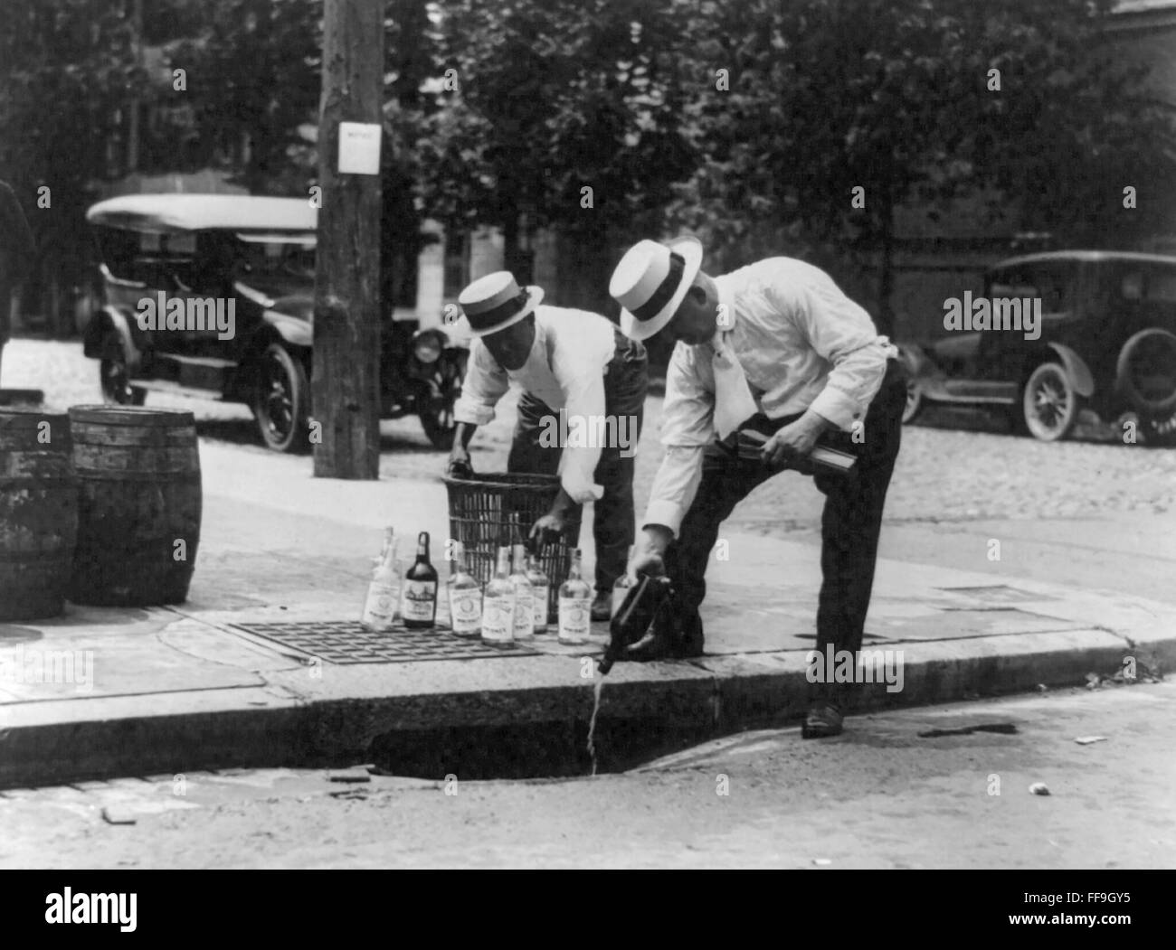 Agents pouring whiskey into sewer during probibition, USA. Photo c.1920-1930 - Stock Image
