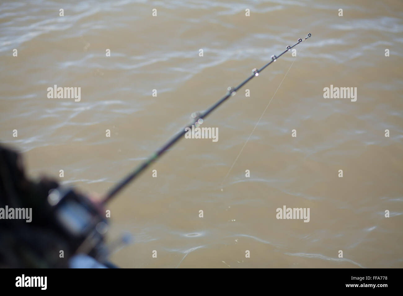 Close up of fishing rod in murky water - Stock Image
