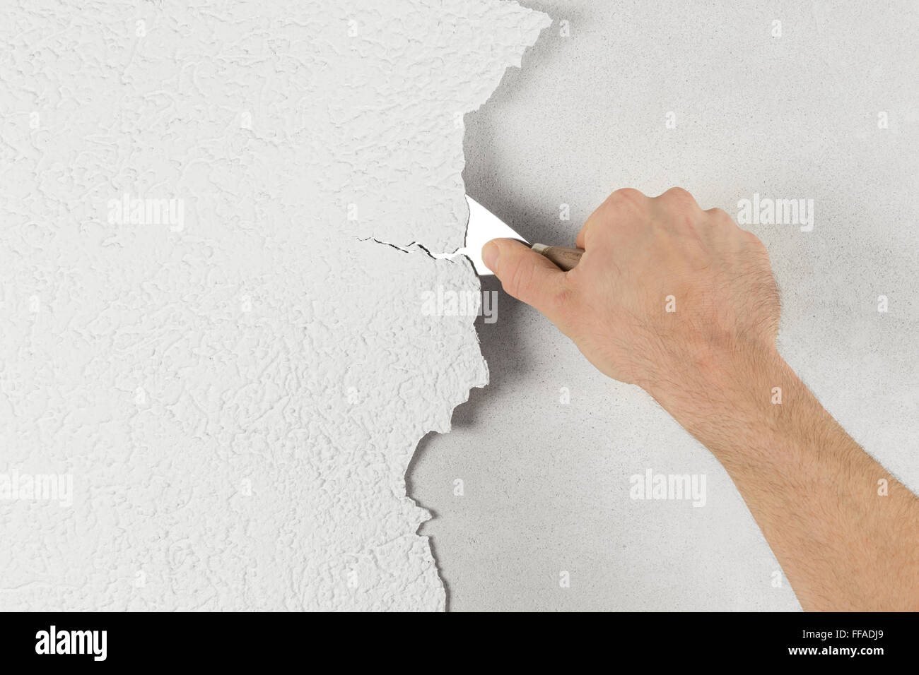 plaster removal with hand and spatula - Stock Image