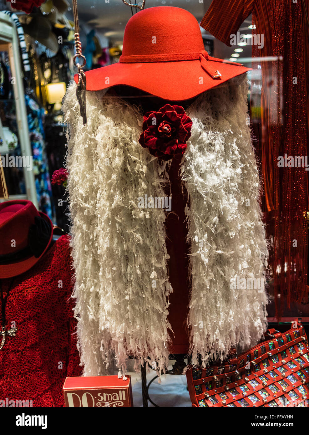 Woman's red hat and frilly white unusual vest, that could be worn as an over-the-top-scarf displayed in a clothing - Stock Image