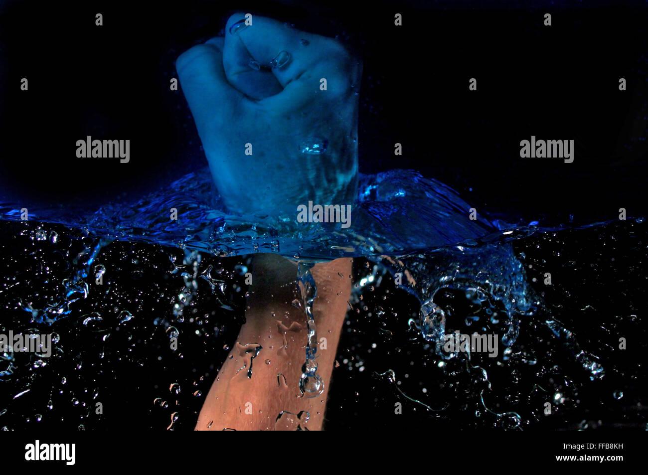 Hand smashing through water - Stock Image