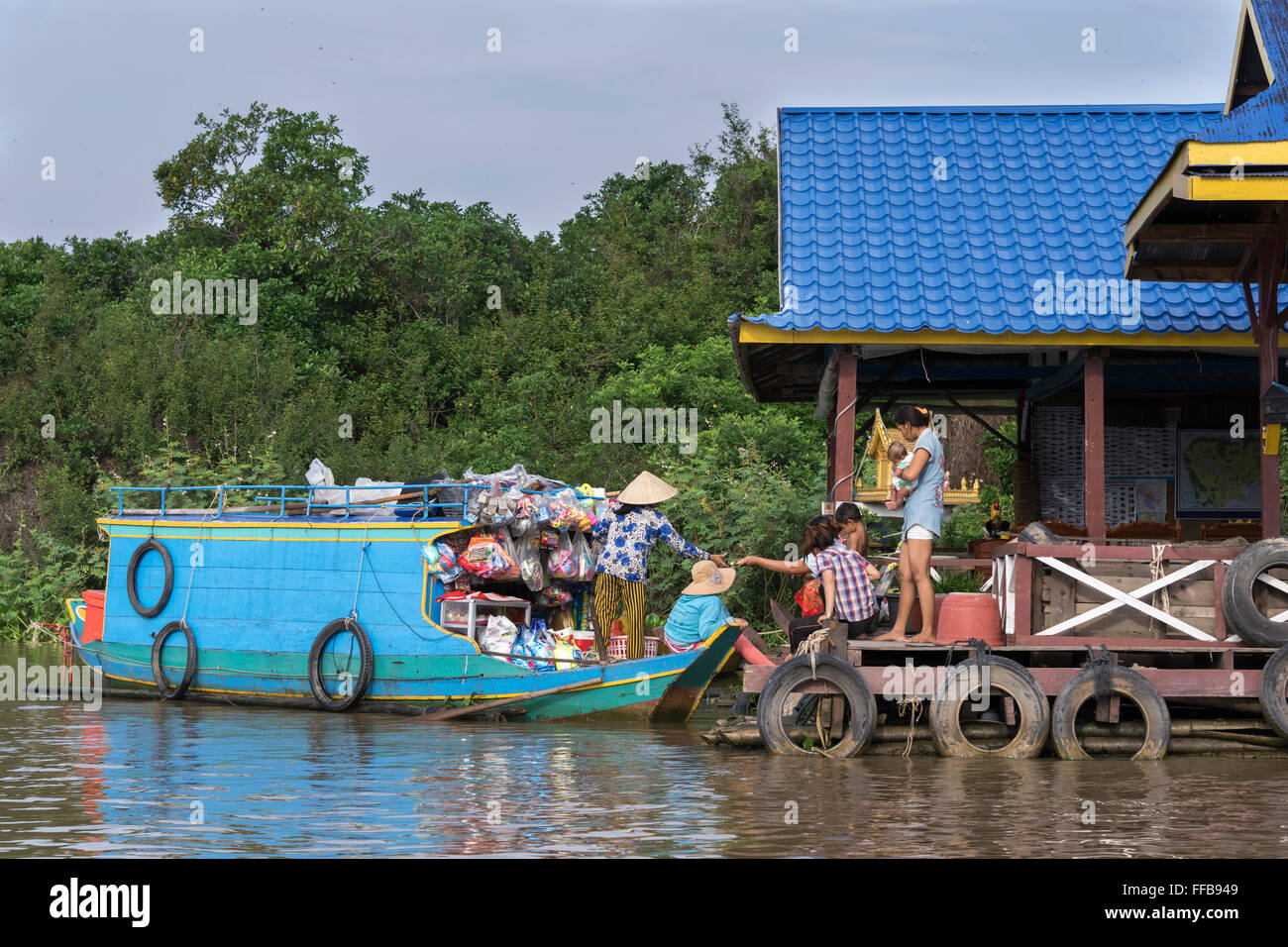Buying goods from the odds and ends boat, Chong Khneas floating village, Siem Reap River, Cambodia - Stock Image