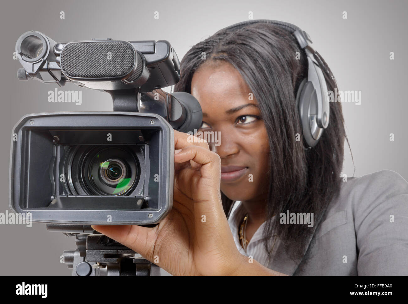 a young African American women with professional video camera and headphone 6357410787