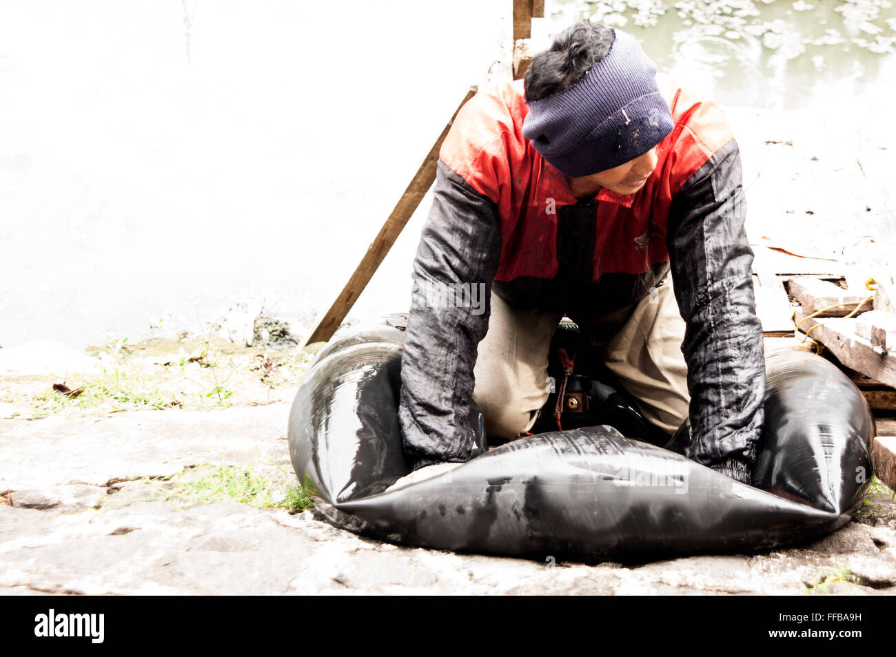 Jakarta, Indonesia. 11th Feb, 2016. Fish Hunter sprucing factitious canoe at River side in Jakarta, Indonesia. Fishes Stock Photo